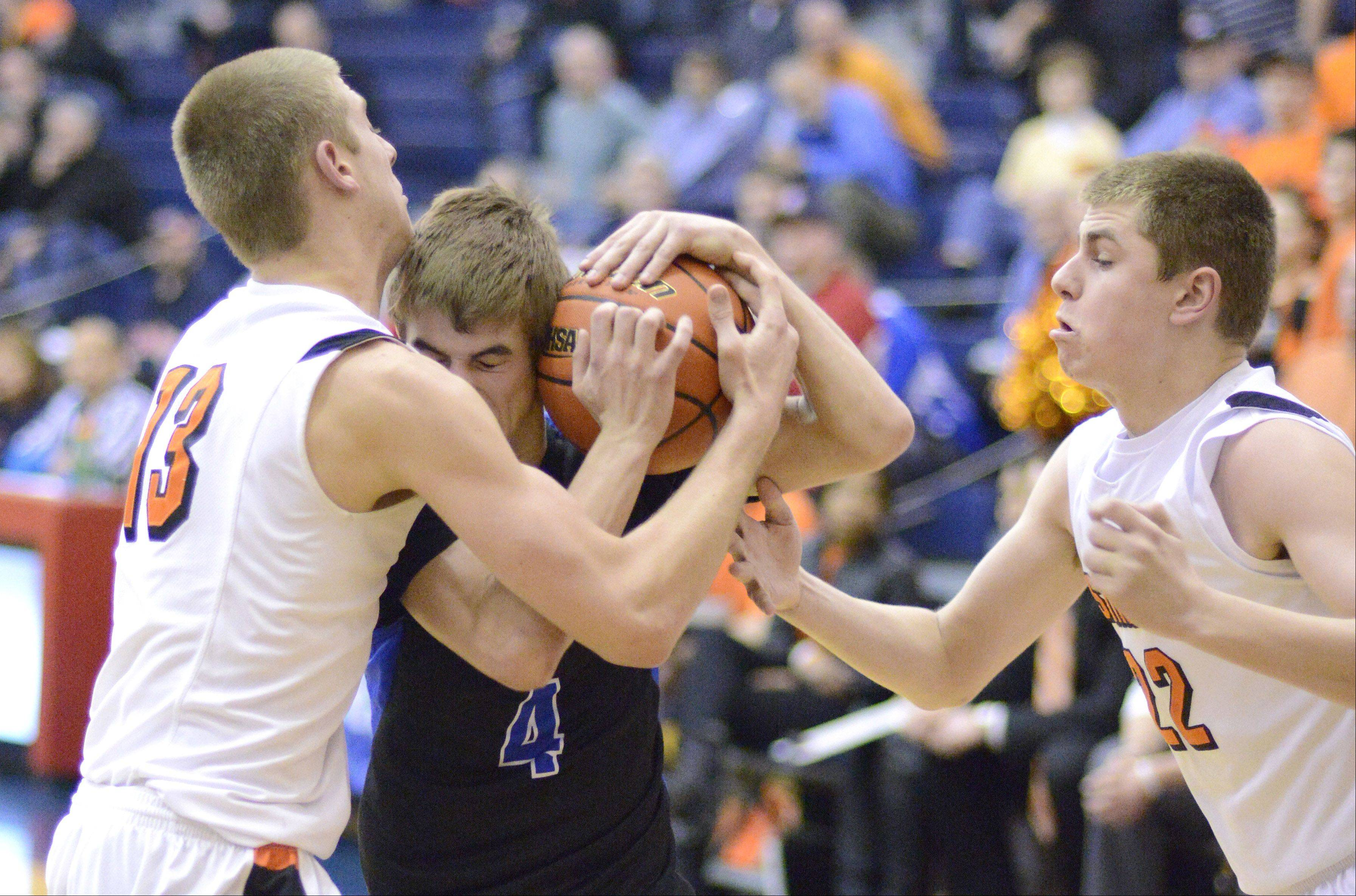 St. Charles North's Jake Ludwig wrestles with St. Charles East's Ben Skoog and James McQuillan until a foul is called on the Saints in the third quarter of the Class 4A regional on Wednesday, February 27.
