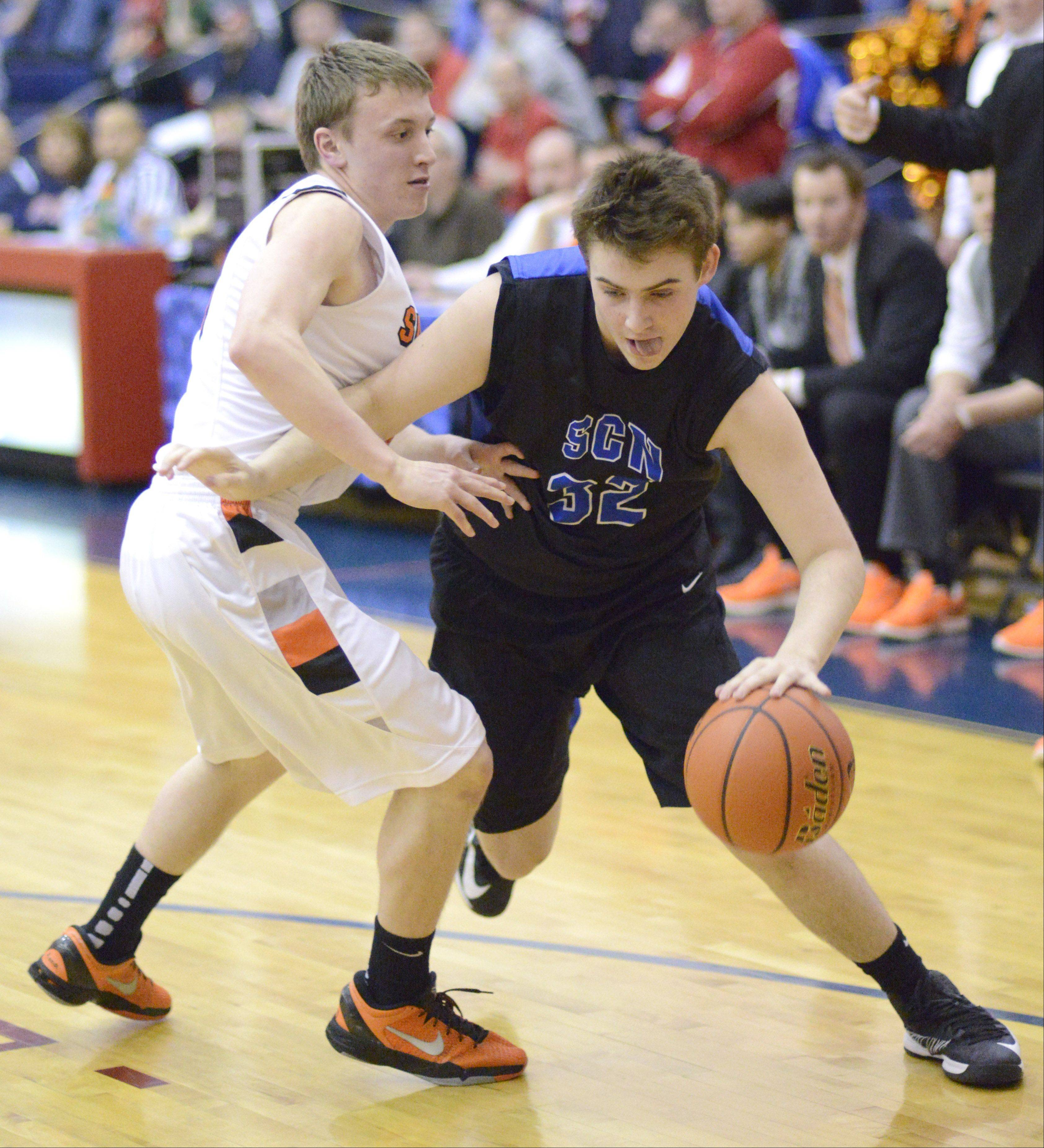 St. Charles North's Jack Callaghan maneuvers around St. Charles East's Ethan Griffiths in the second quarter of the Class 4A regional on Wednesday, February 27.