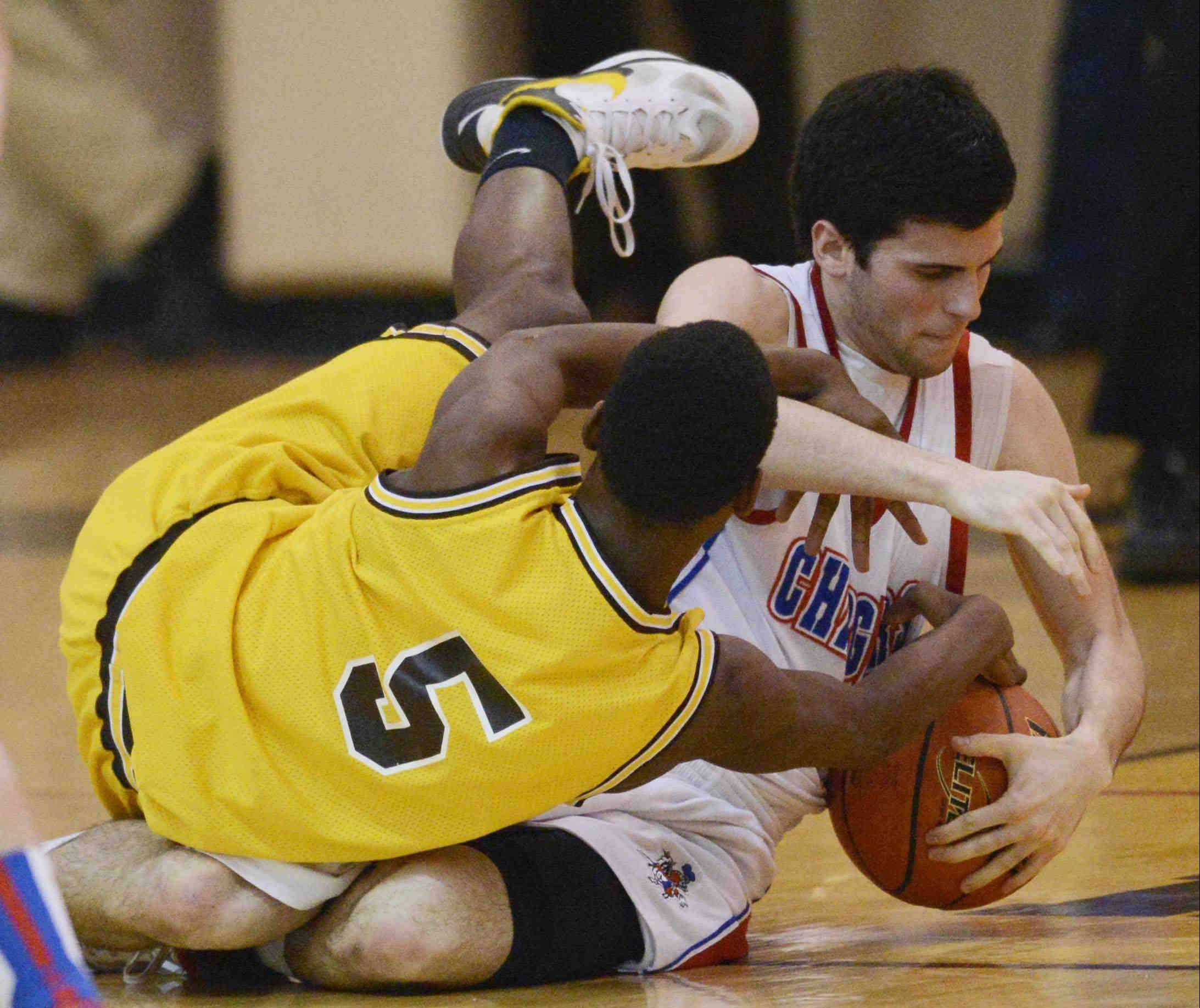 Jacobs' Chrishawn Orange (5) and Dundee-Crown's Trent Muscat tangle on the floor during the Class 4A Jacobs regional semifinal Wednesday night.