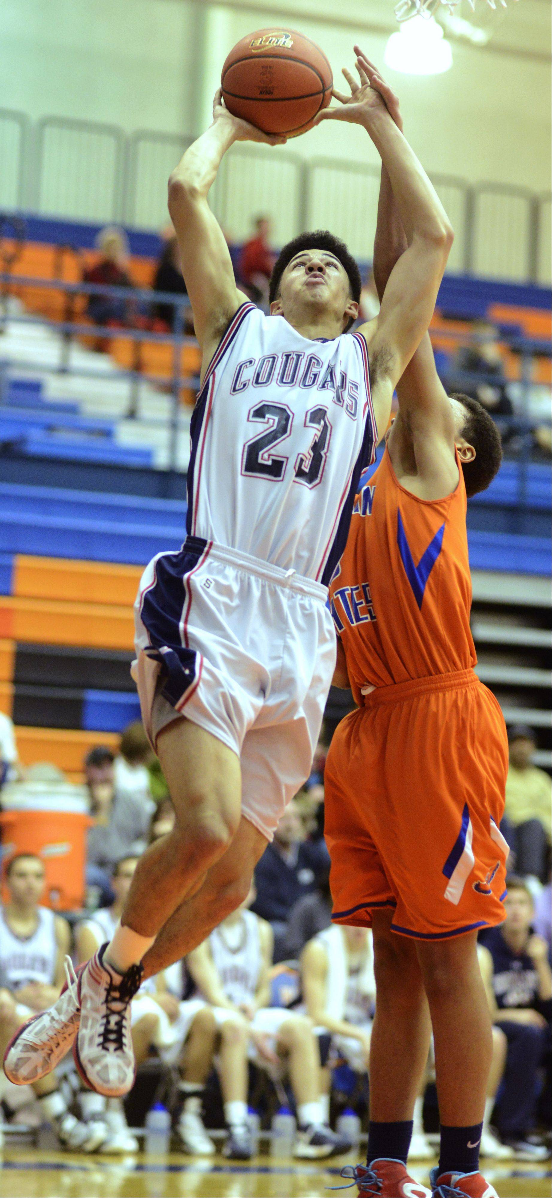 Conant's Robert Hudson, left, drives to the basket for a layup as Hoffman Estates' Jordan Robinson defends.