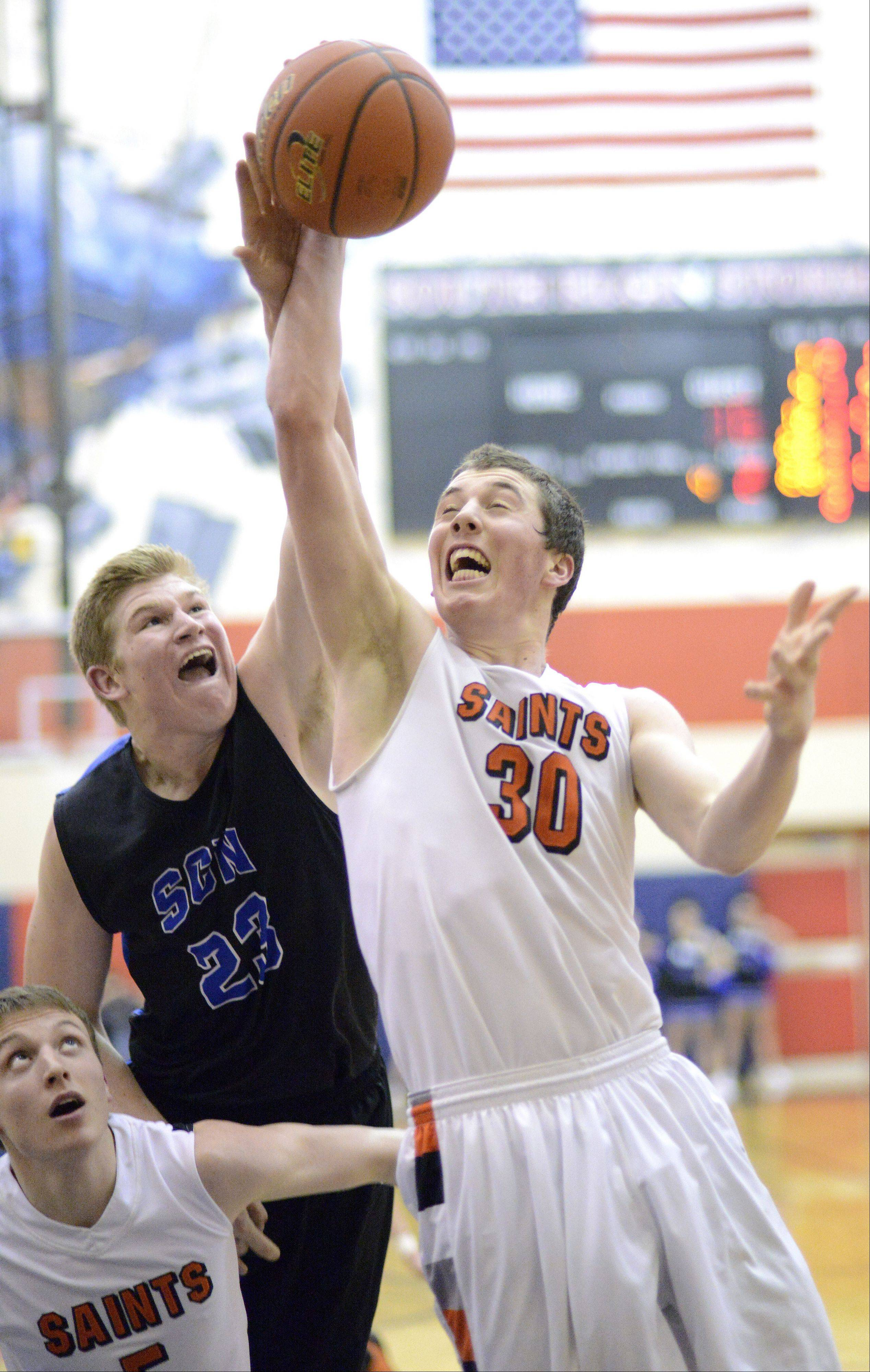 St. Charles North's Justin Stanko tries to swat the ball out of the hands of St. Charles East's David Mason in the third quarter.