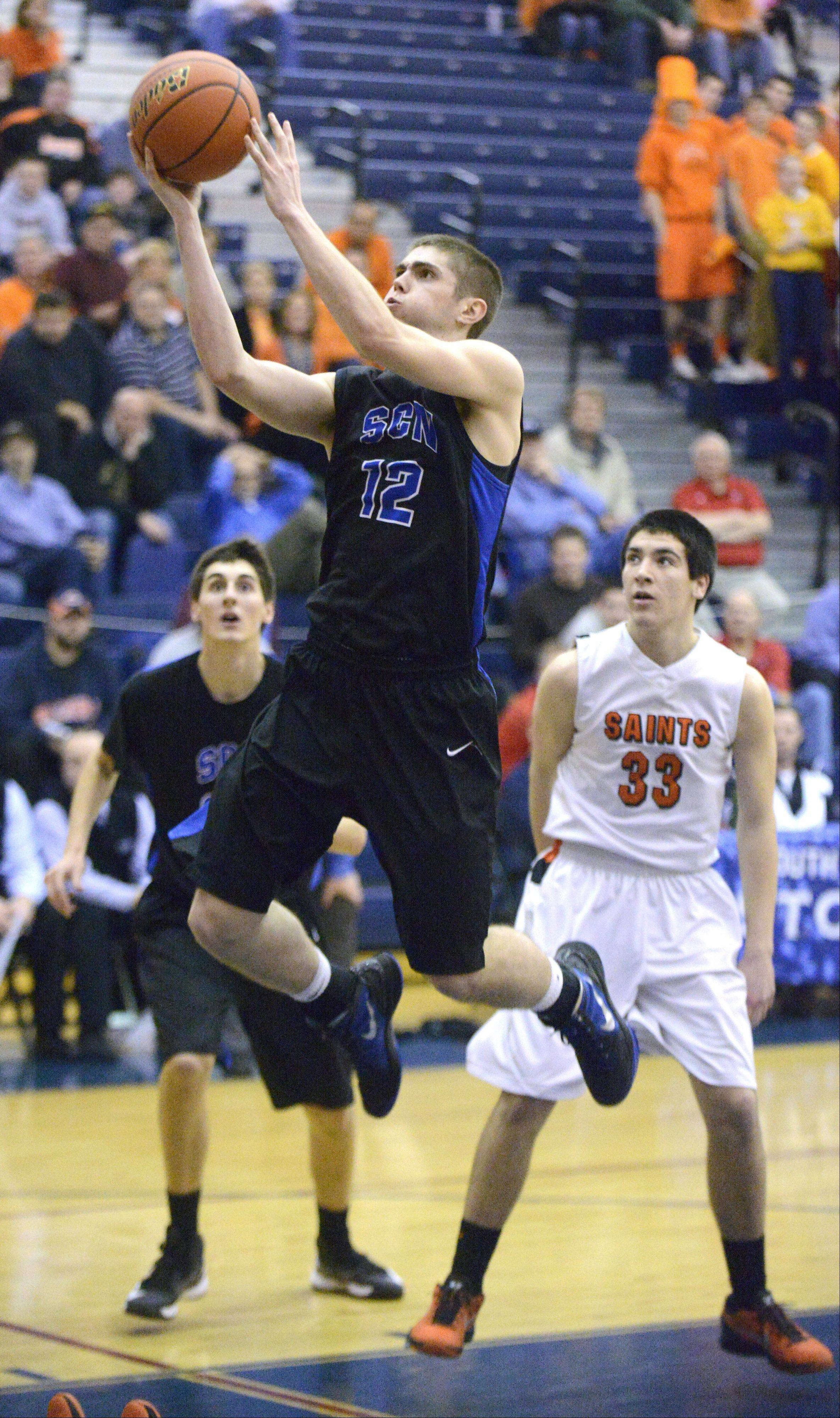 St. Charles North's Quinten Payne soars to the hoop past St. Charles East's Jake Asquini in the fourth quarter.