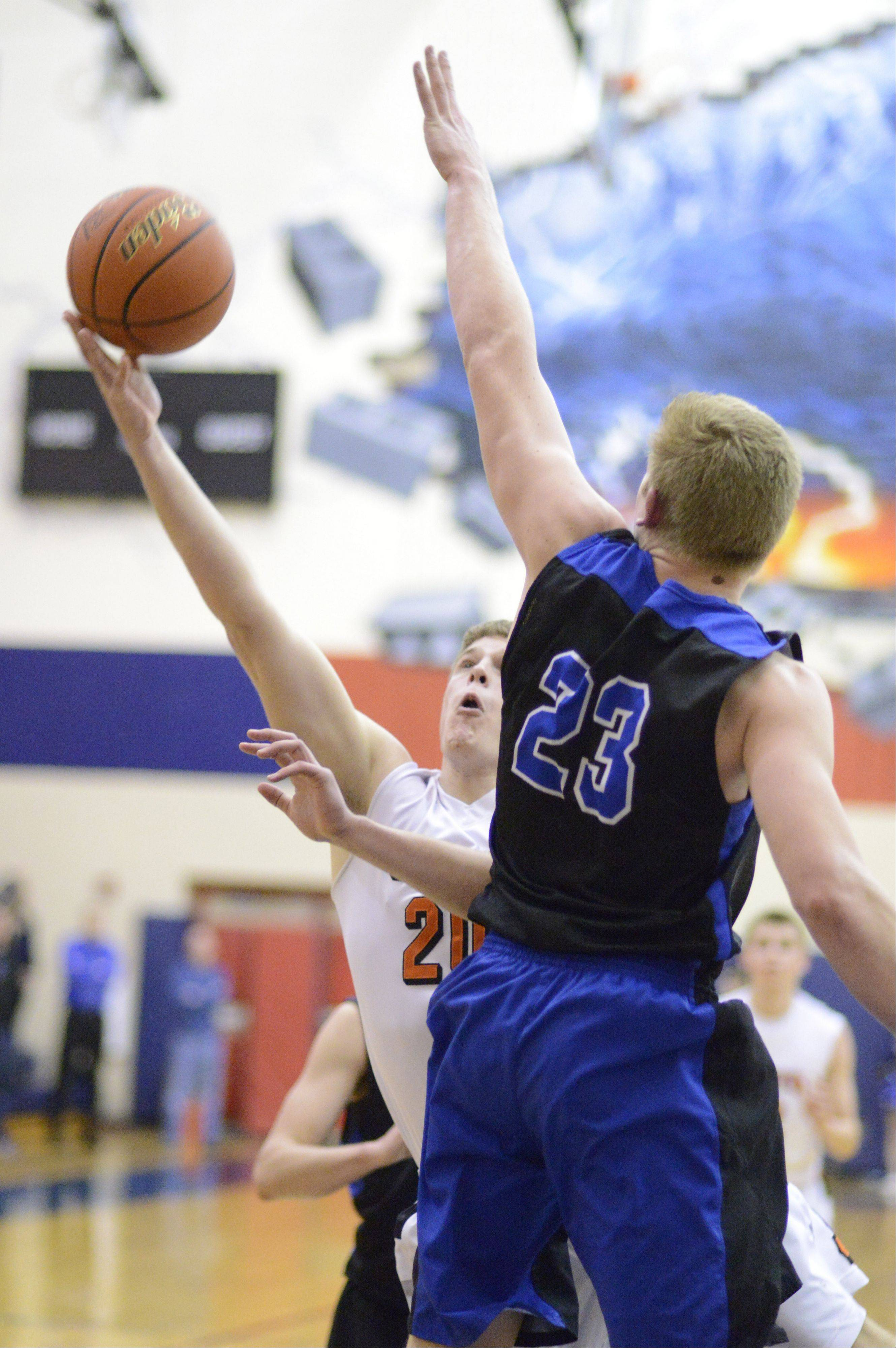 St. Charles East's Tyler Windau shoots around a block by St. Charles North's Justin Stanko in the third quarter.