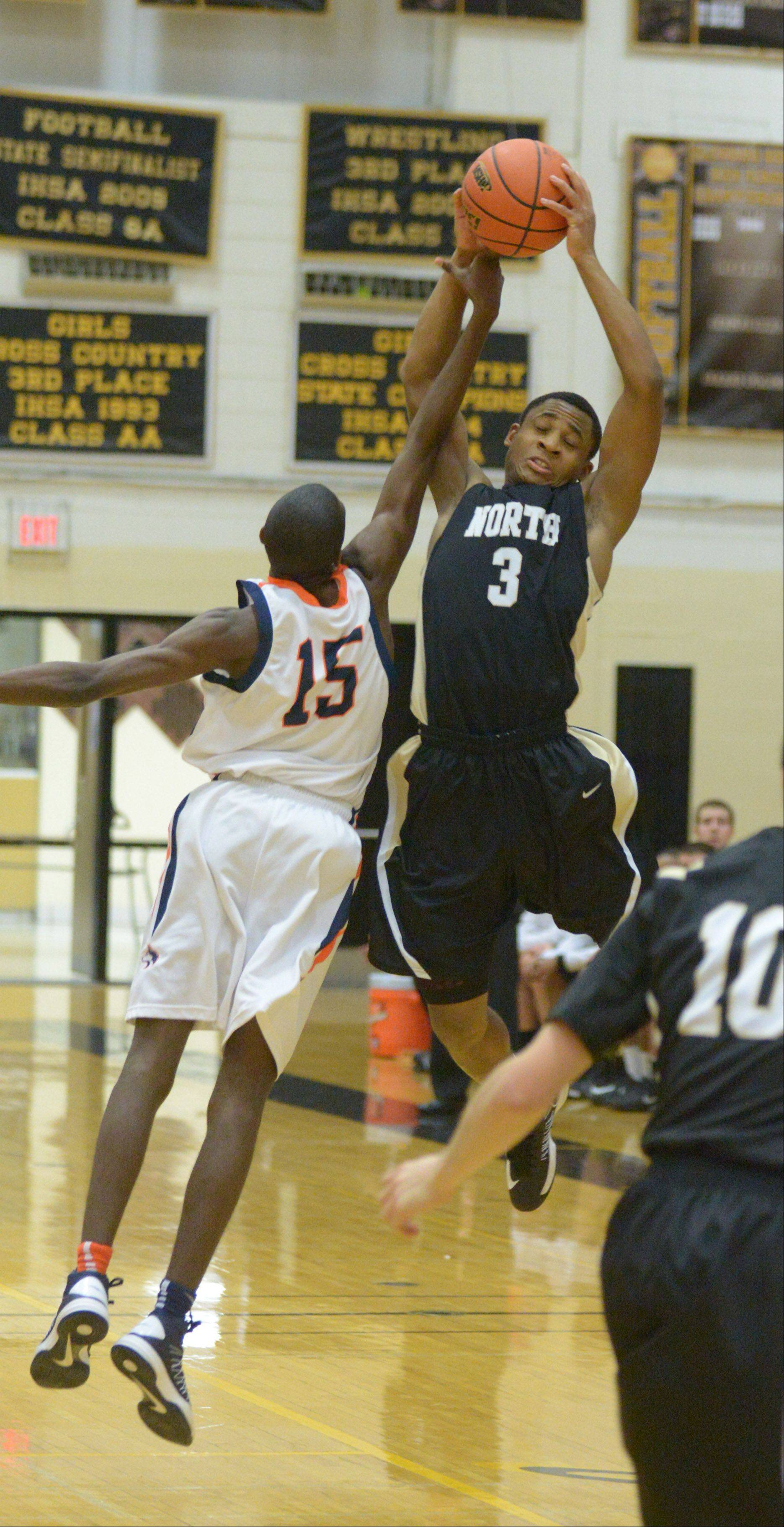 Jason Gant of Oak Park-river Forest tries to block a shot from Justin Jackson of Glenbard North .