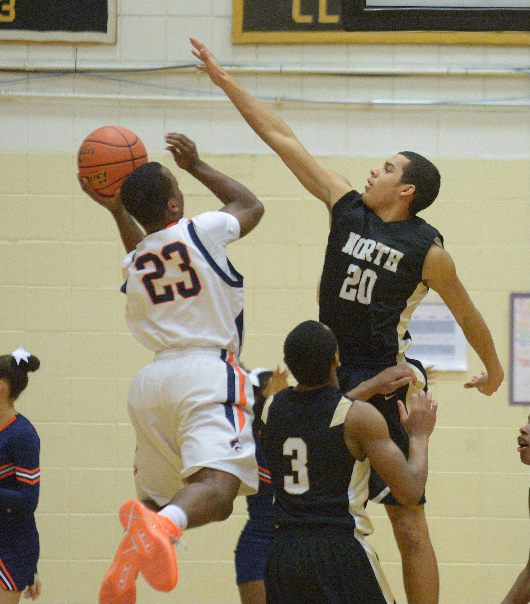 Erik Locke of Oak Park-River Forest puts up a shot while Kendall Holbert of Glenbard North blocks.