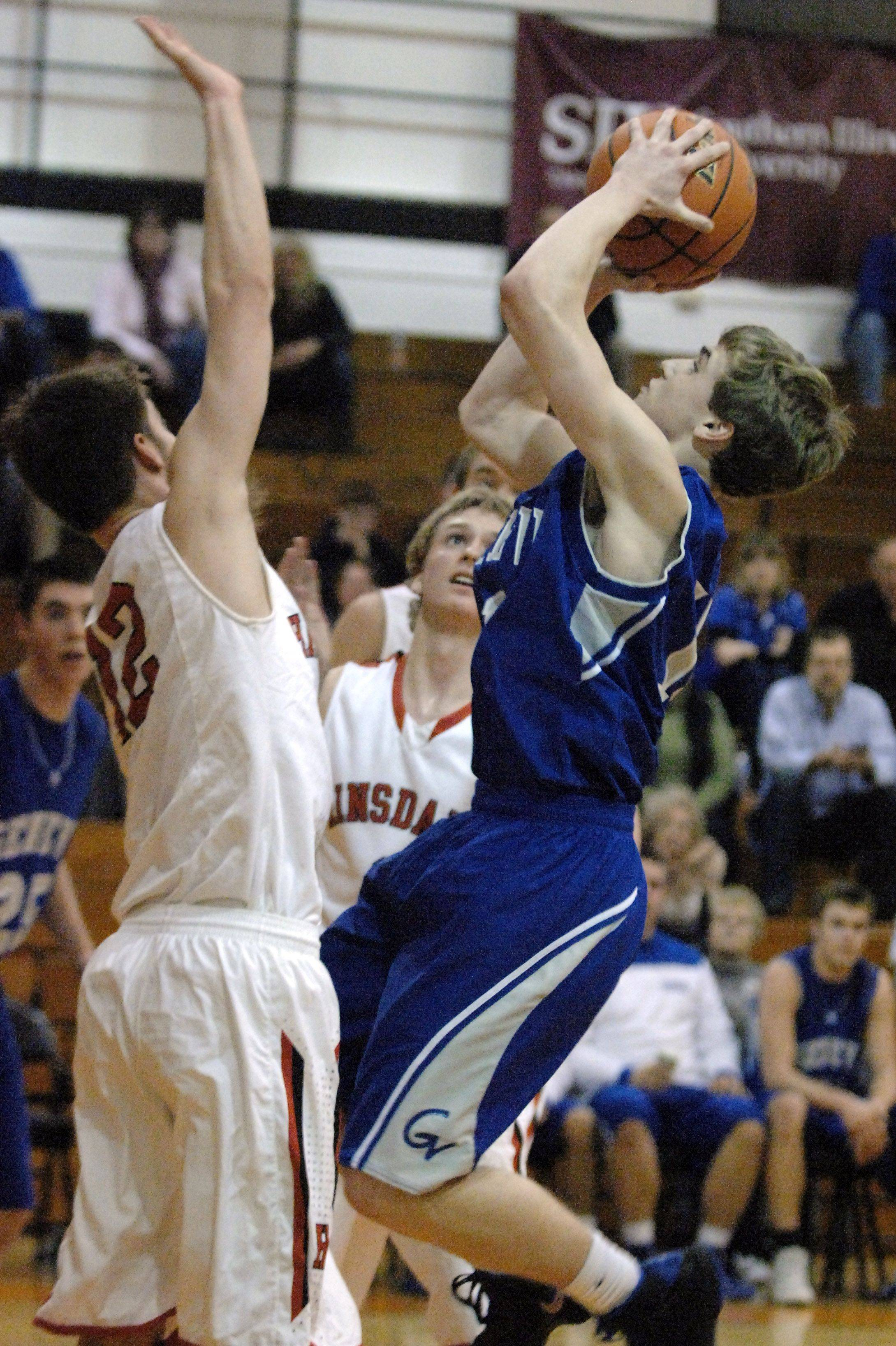 Geneva's Cam Cook scores and is fouled by Hinsdale Central's Matt Rafferty.