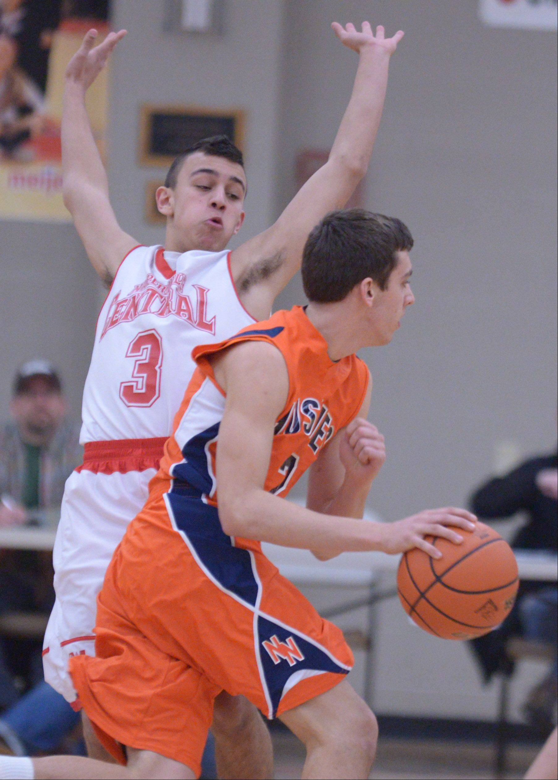 Anthony Rehayem of Naperville North pushes his way past Nicky Lopez of Naperville Central. This took place during the Naperville North vs. Naperville Central Class 4A Benet boys basketball regional semifinal game Thursady.