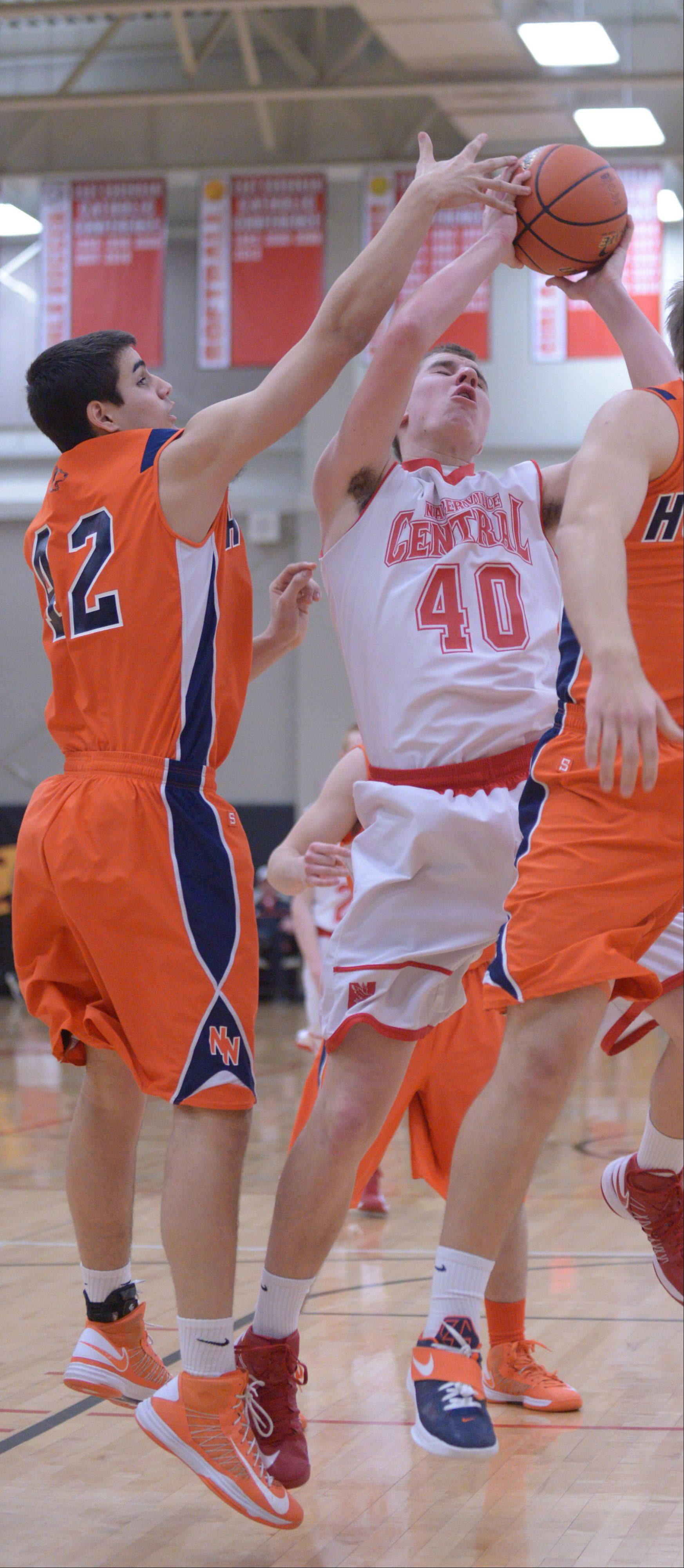 Rafee Mahmud of Naperville North and Patrick Maloney of Naperville Central go for a rebound .