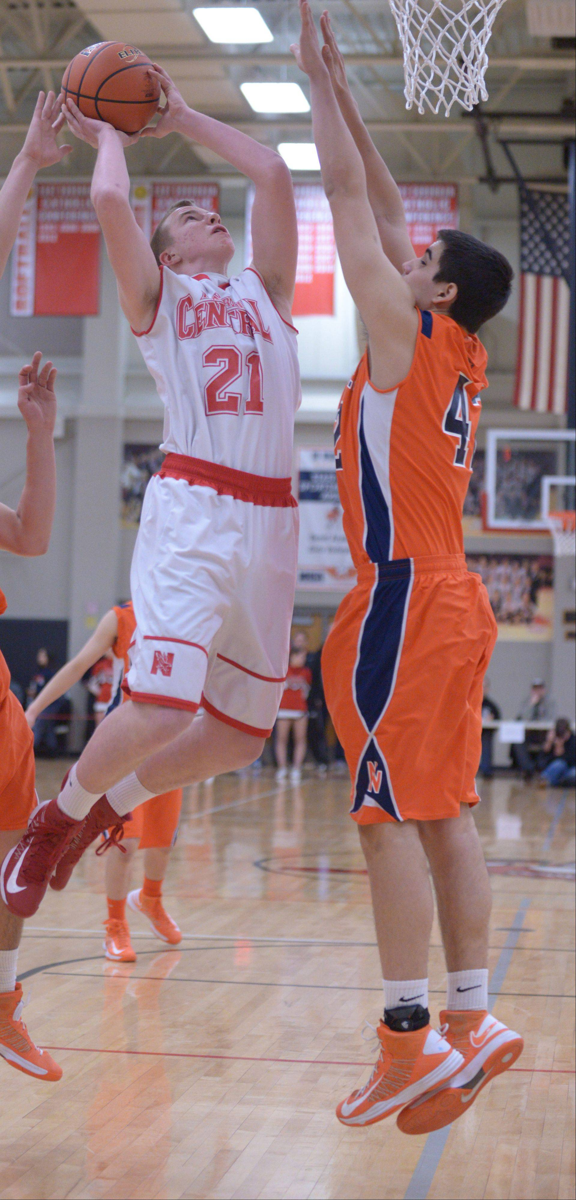 Mike Blaszczyk of Naperville Central puts up a shot while Rafee Mahmud of Naperville North blocks.