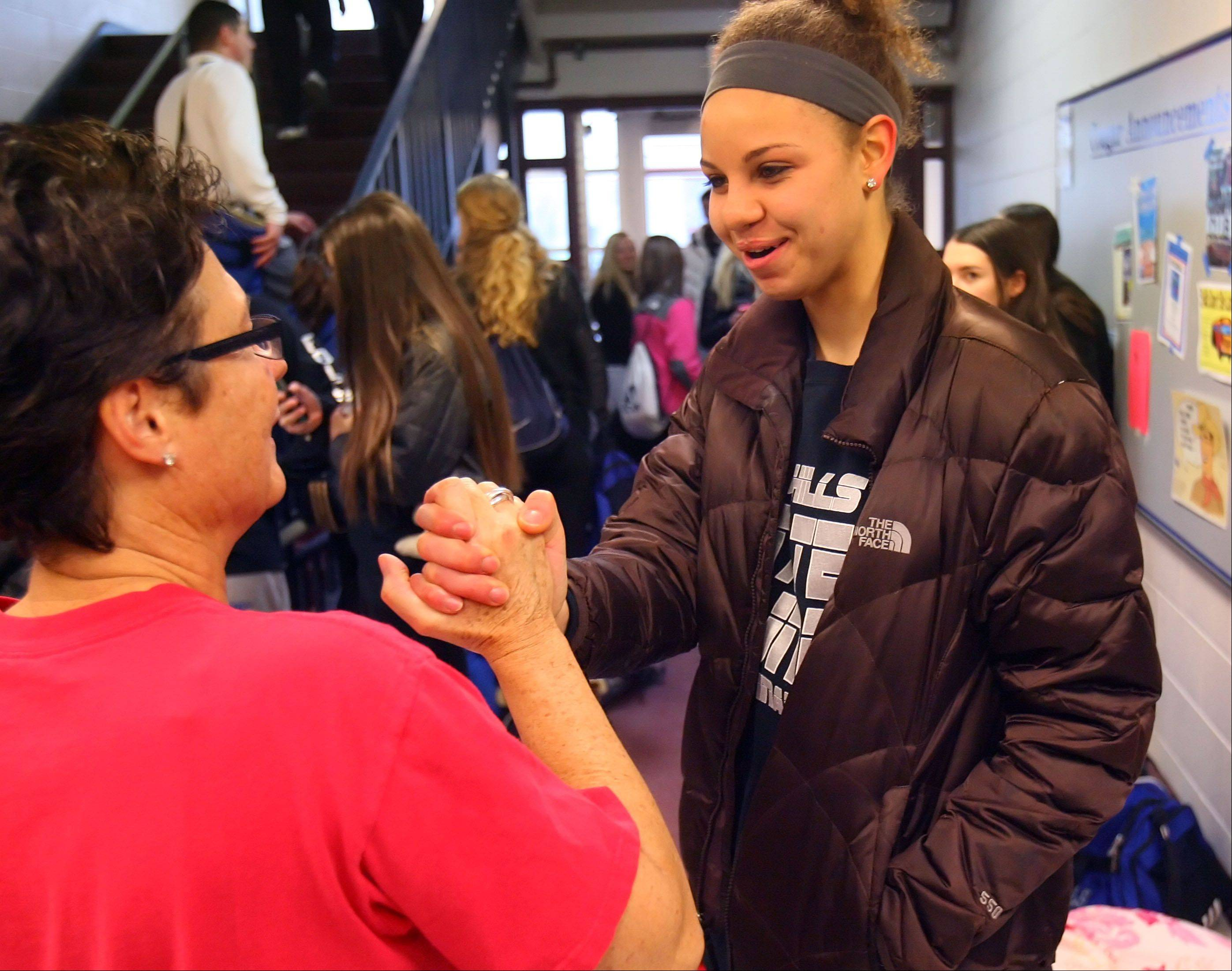 Vernon Hills High School Principal Ellen Cwick, left, gives Lauren Webb some words of encouragement as the girls basketball team gets ready to leave for the Class 3A girls state basketball tournament at Redbird Arena in Normal.