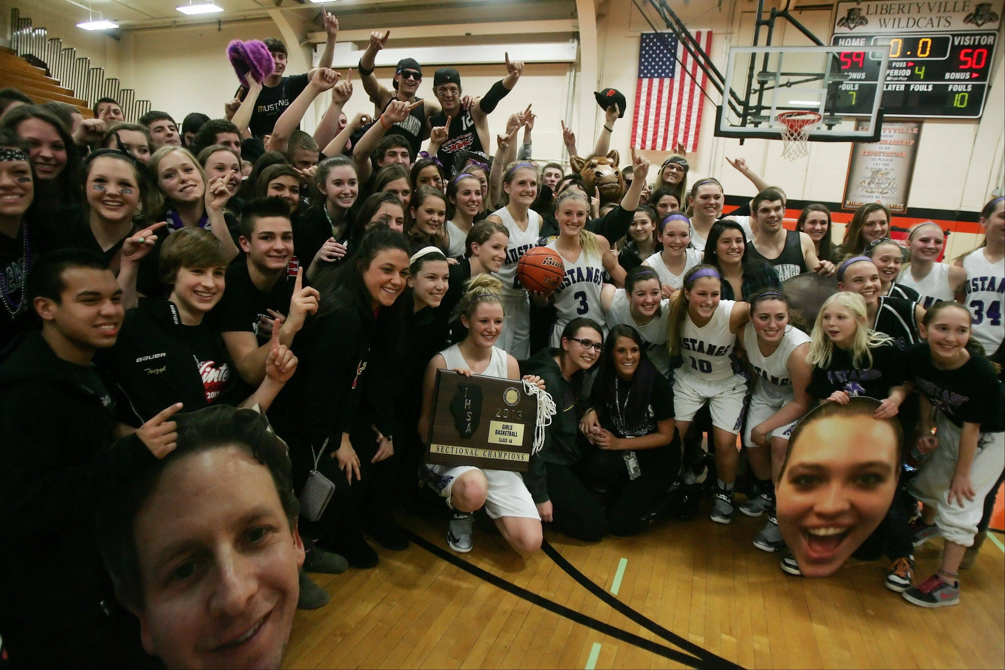 The Rolling Meadows girls basketball team celebrates after winning the sectional final on Feb. 21 in Libertyville. The team will play in the state tournament Friday night.