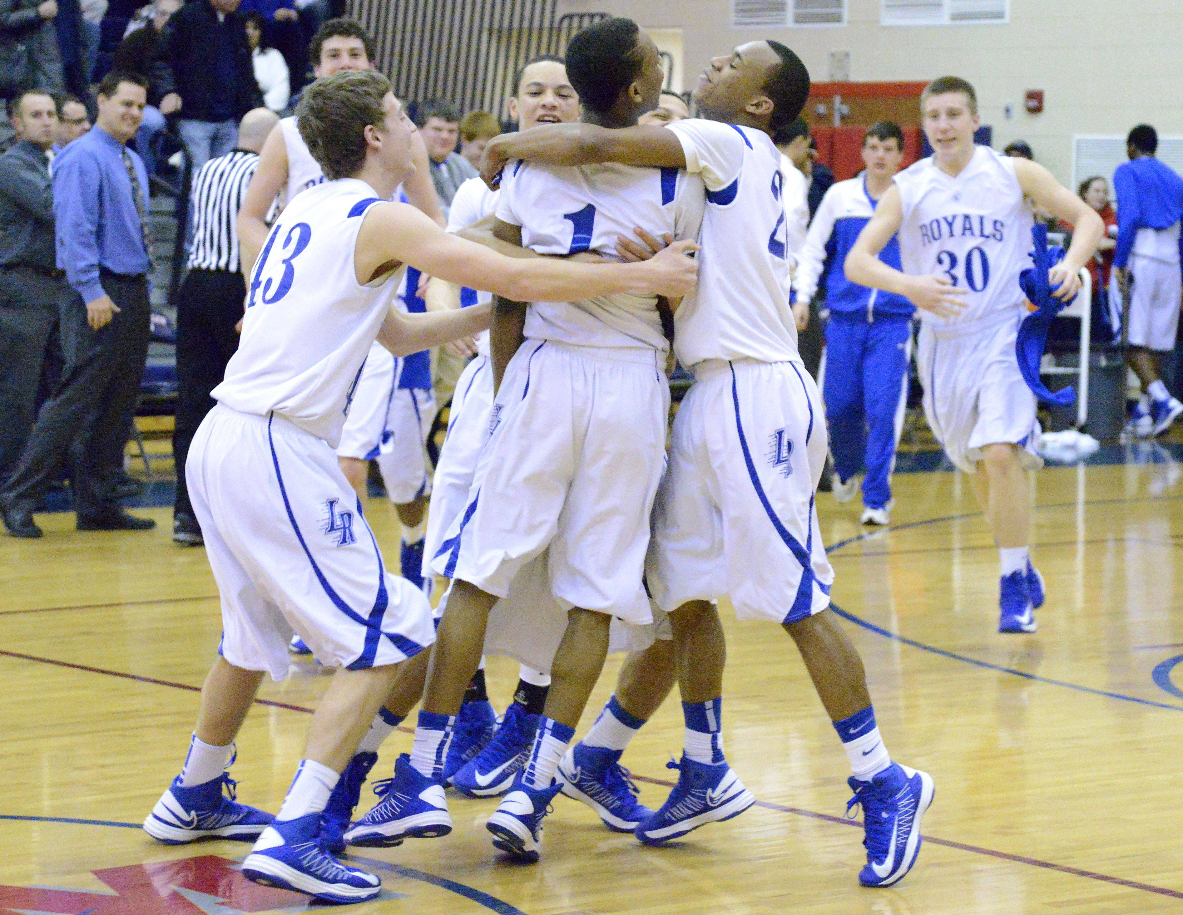Larkin's Jack McCracken, Quantice Hunter, Quentin Ruff and teammates embrace after their win over St. Charles North in the Class 4A regional championship game on Friday, March 1.