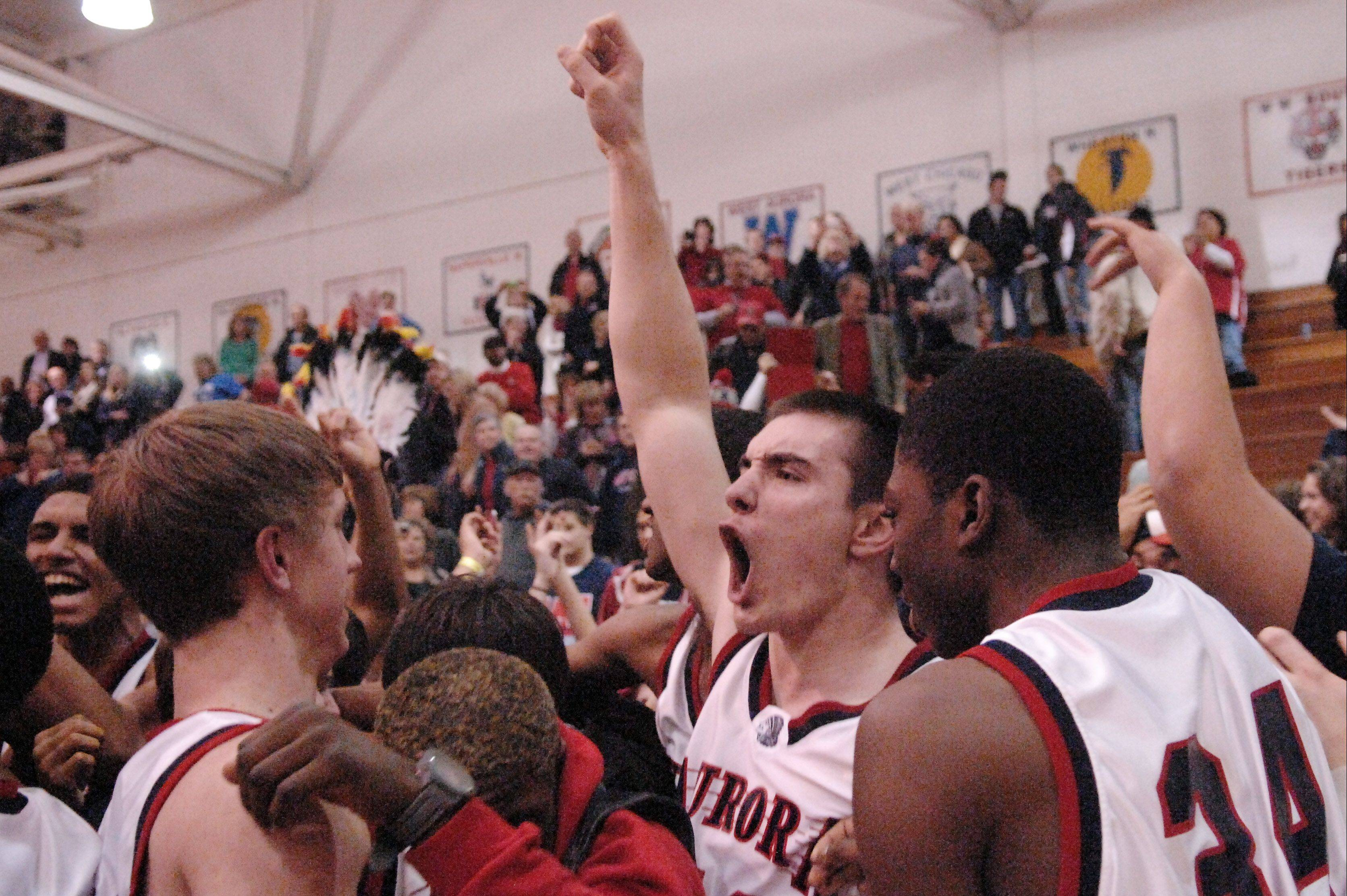 West Aurora's Spencer Thomas (40, arm raised} and his teammates celebrate with fans following their win over Geneva during Friday's regional final in Wheaton.