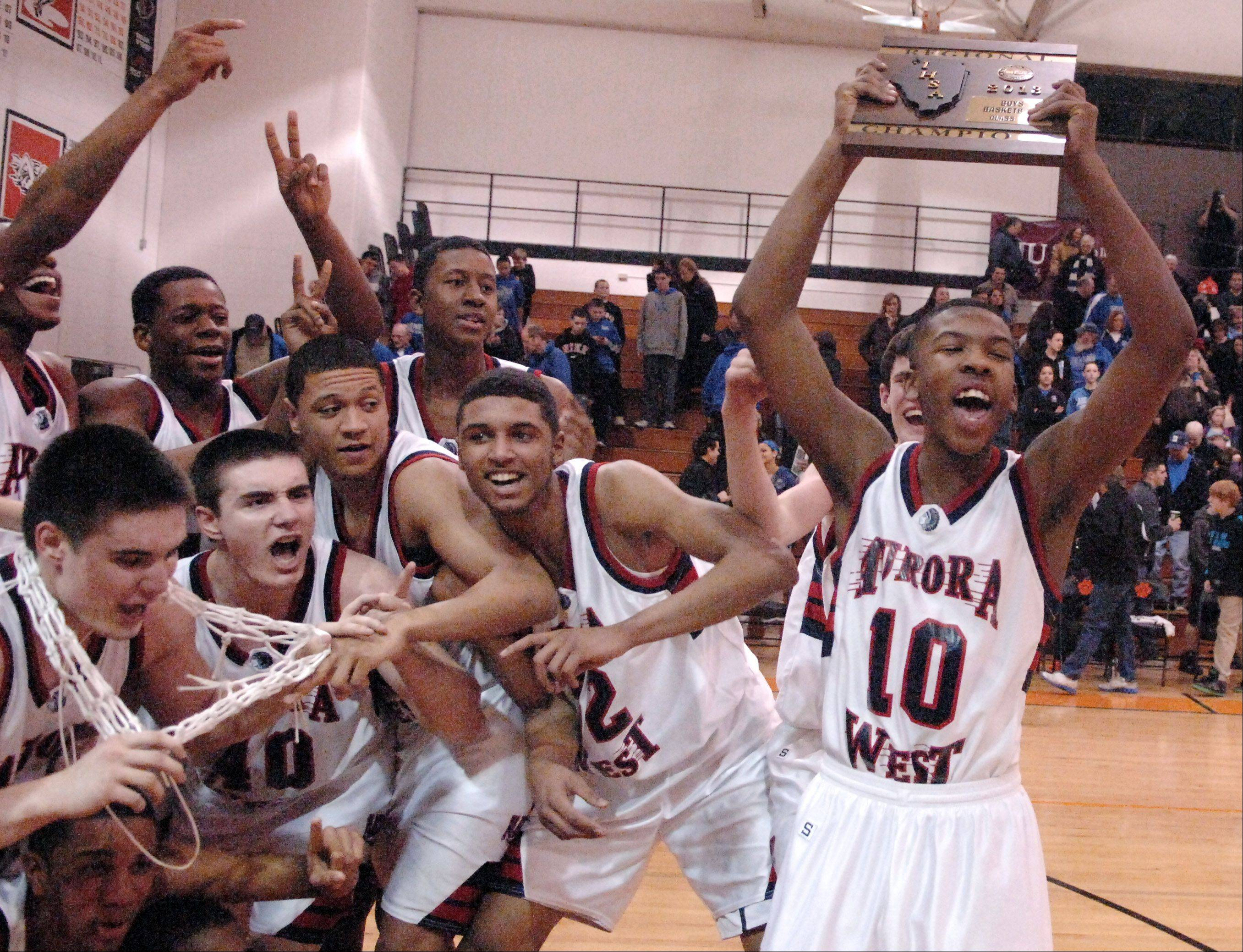 West Aurora's Jontrell Walker (10) is the first to get his hands on the regional championship plaque as his teammates post for pictures following their win over Geneva during Friday's regional final in Wheaton.