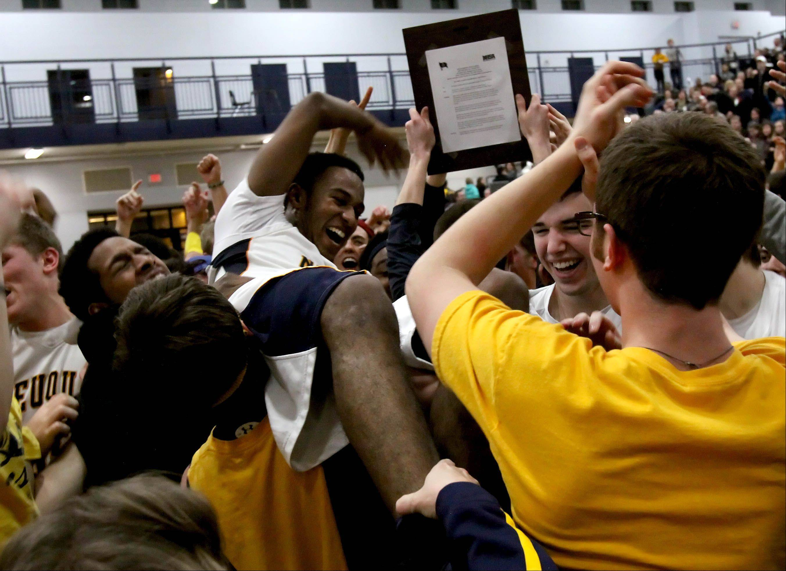Jabari Sandifer of Neuqua Valley gets lifted up by the fans after they beat Waubonsie Valley 69-61 in Class 4A boys basketball regional finals at Oswego East on Friday.