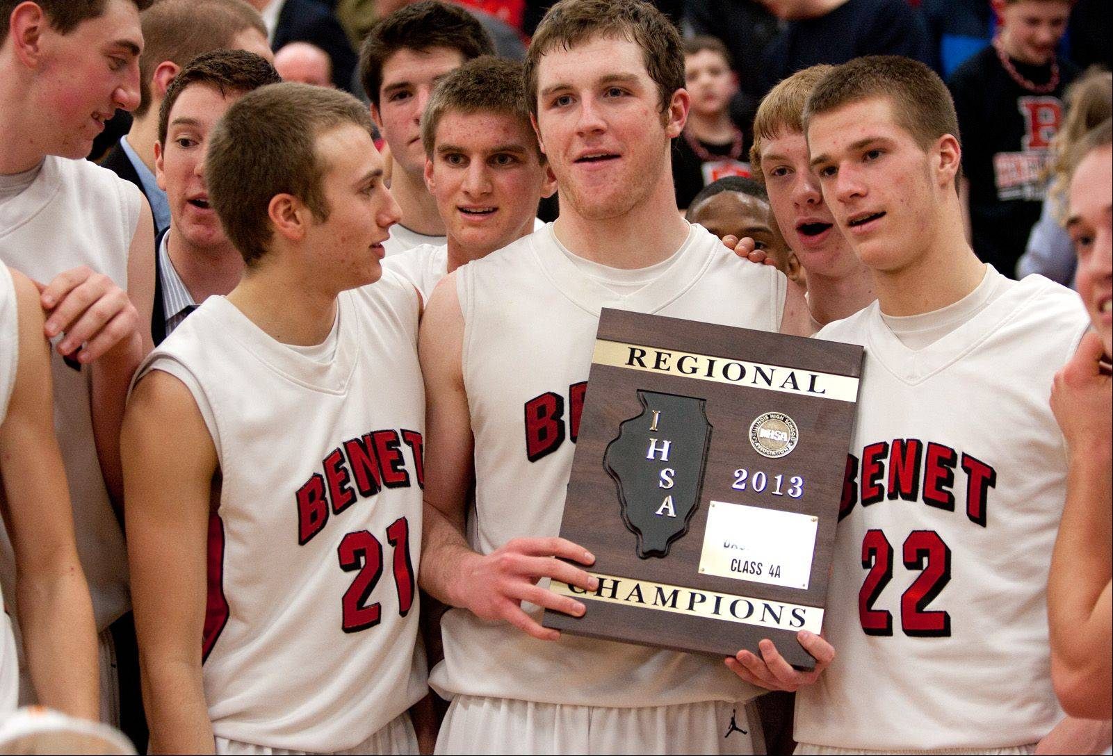 Benet's Pat McInerney holds a regional championship plaque after beating Naperville Central.