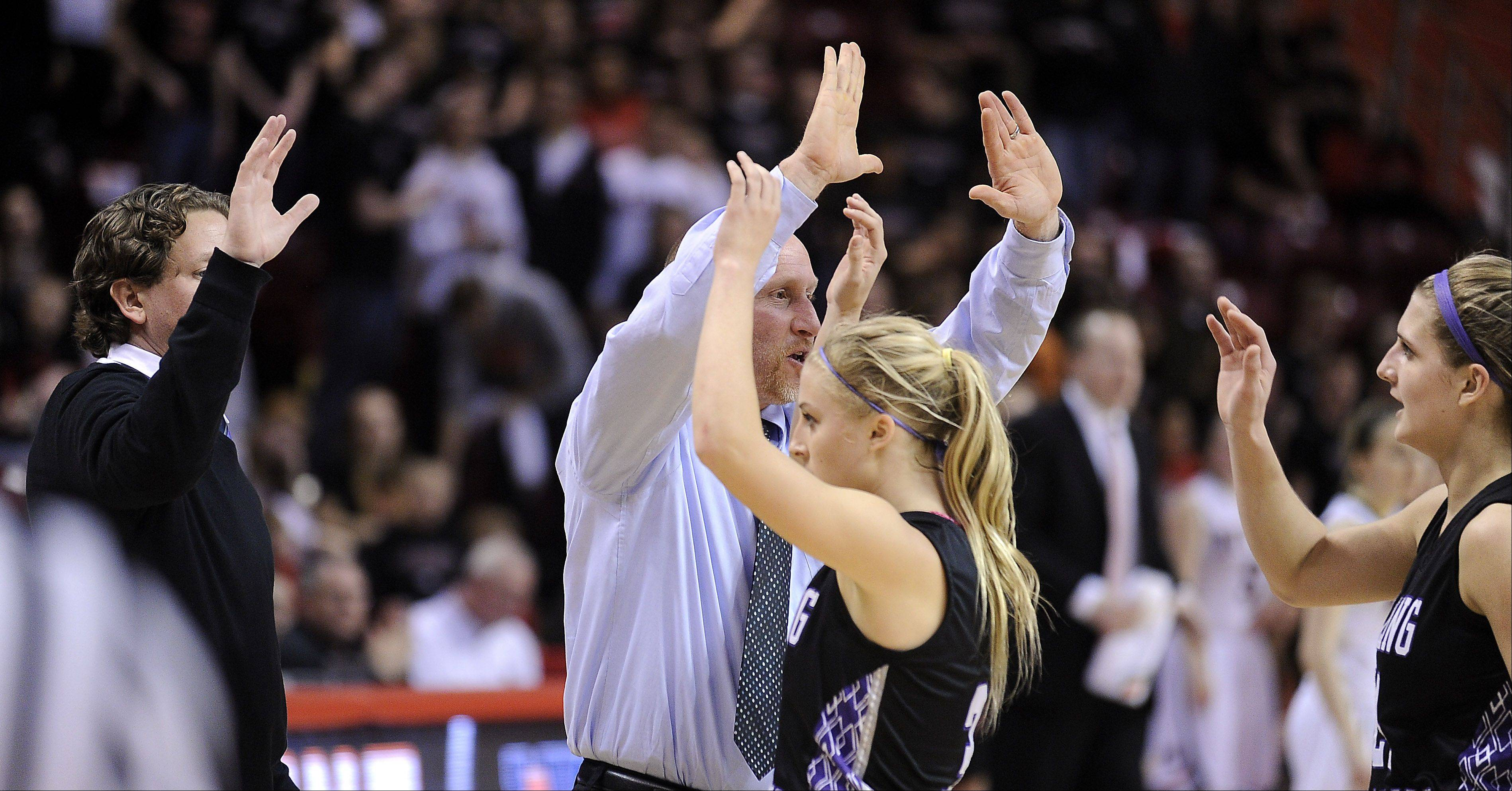 Rolling Meadows' coaches hi-five the starters as they head to the bench in the closing seconds of the game.