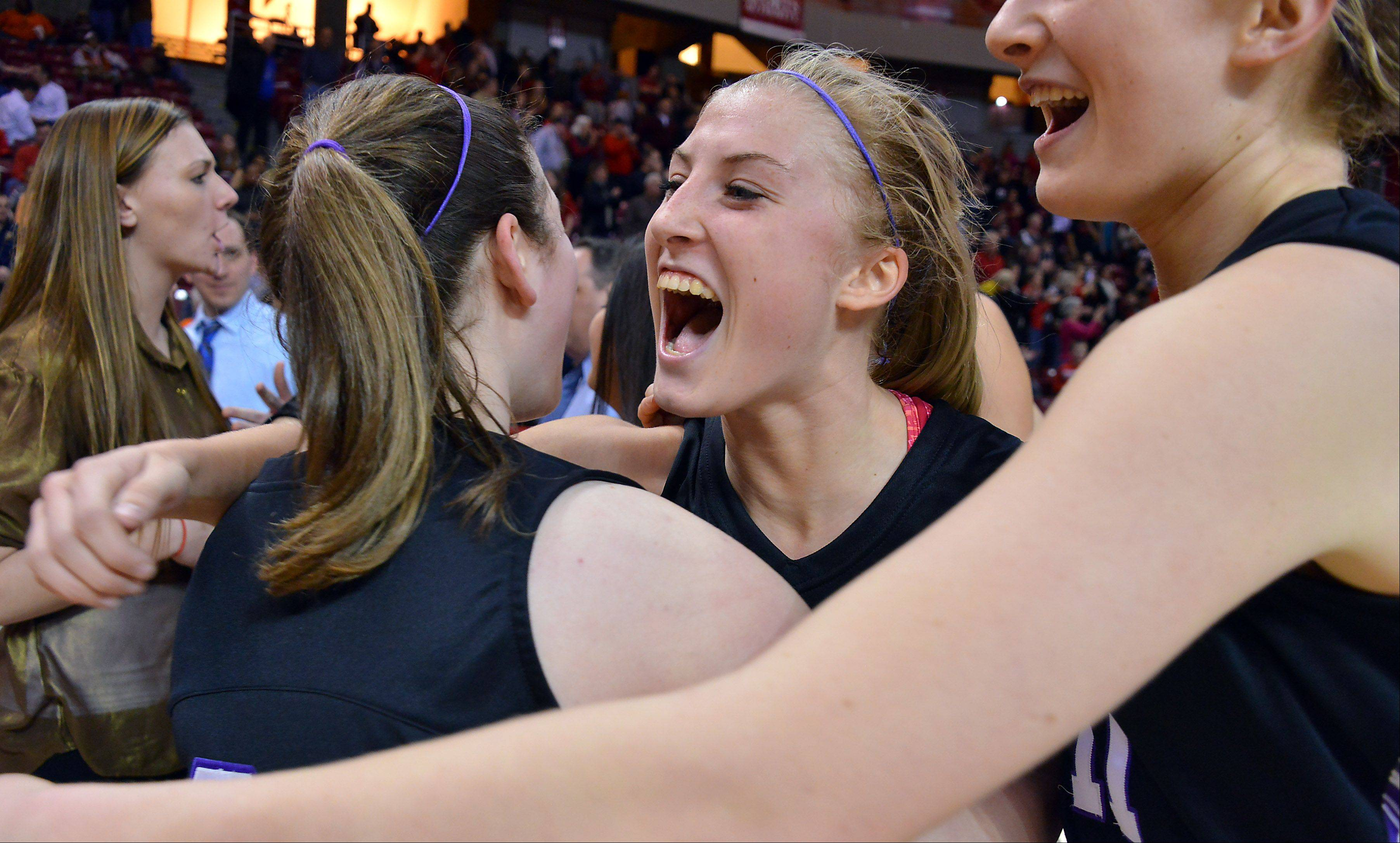 Rolling Meadows' Jackie Kemph is hugged by her teammates at the end of the Class 4A state semifinals after beating Huntley in Normal on Friday.