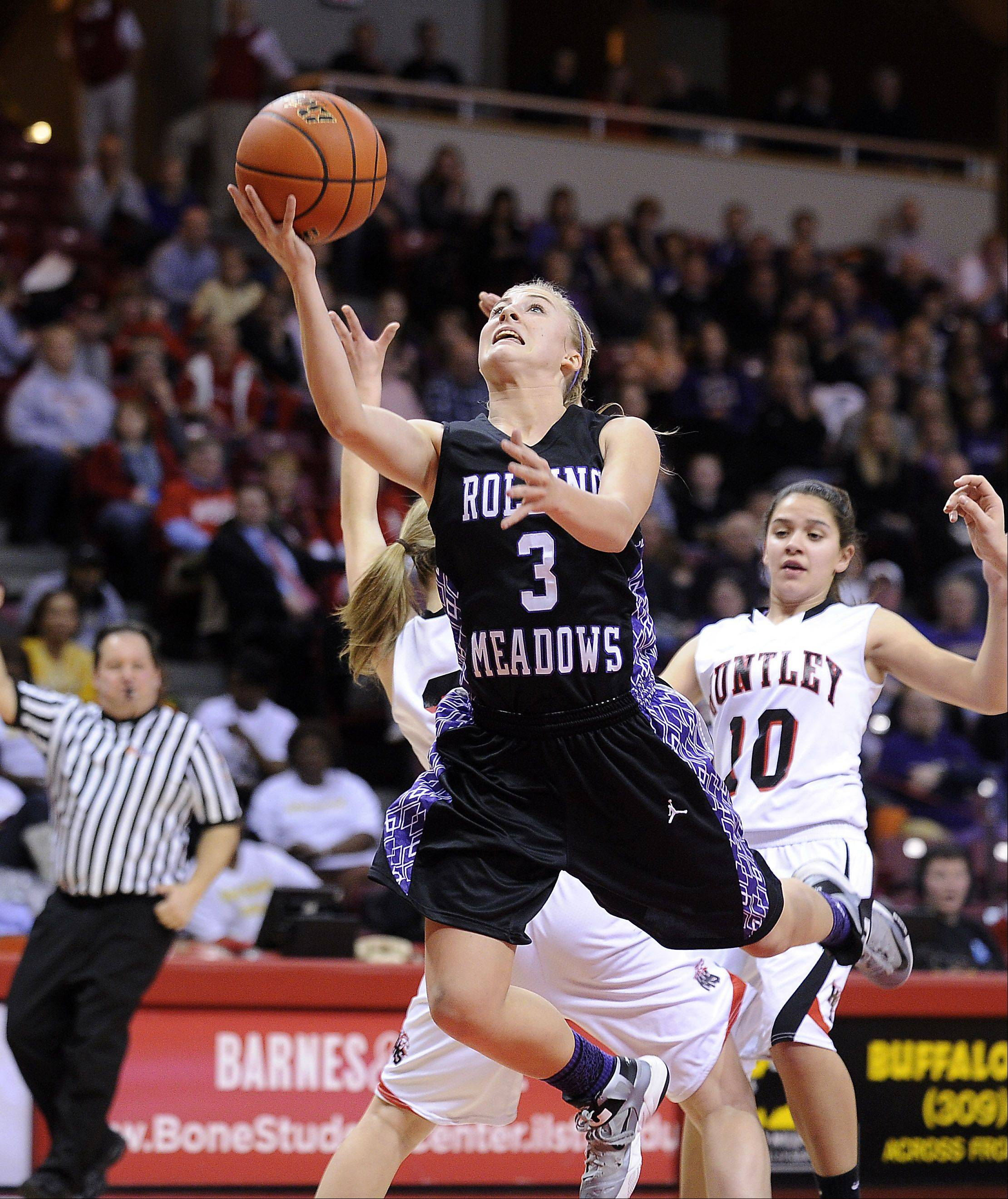 Rolling Meadows' Jackie Kemph delivers to the basket despite pressure from Huntley's defense during the Class 4A girls basketball semifinals in Normal on Friday.