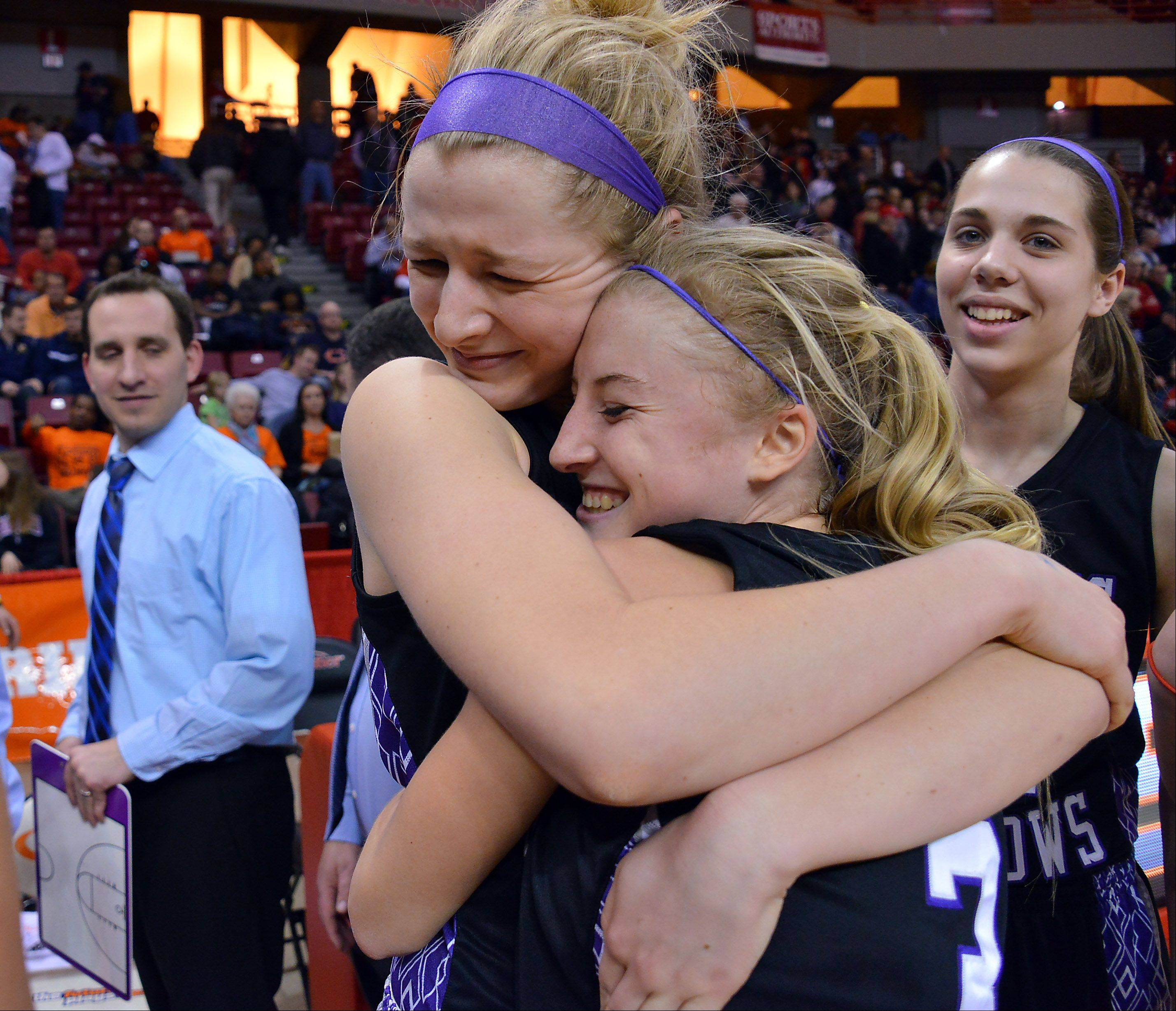 Rolling Meadows' Jackie Kemph is hugged by Jenny Vliet at the end of the Class 4A girls basketball semifinals after beating Huntley in Normal on Friday.