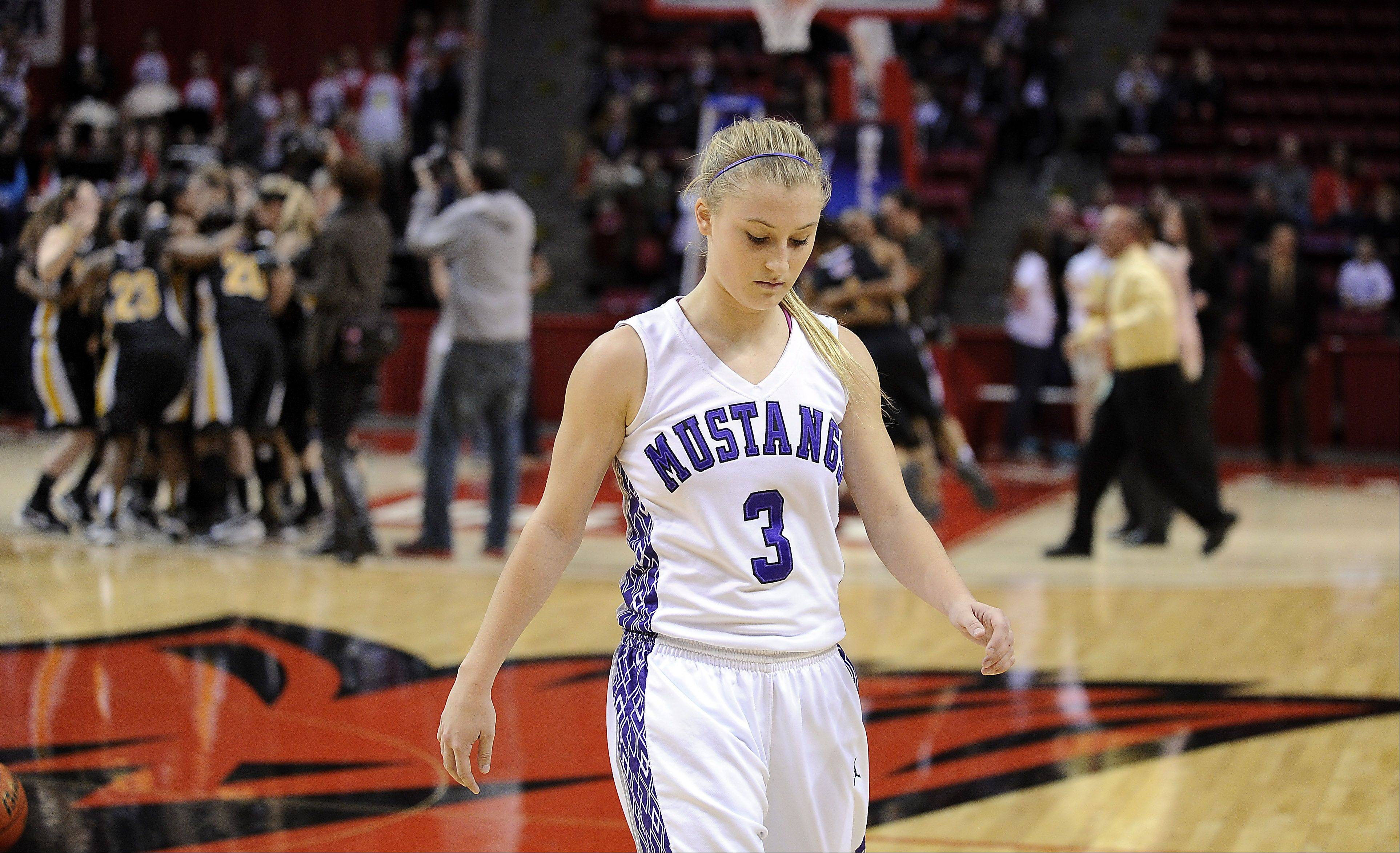 Rolling Meadows Jackie Kemph walks off the court stunned after a buzzer beater shot by Marian in the final second in the Class 4A 2013 girls basketball championship game in Normal on Saturday.