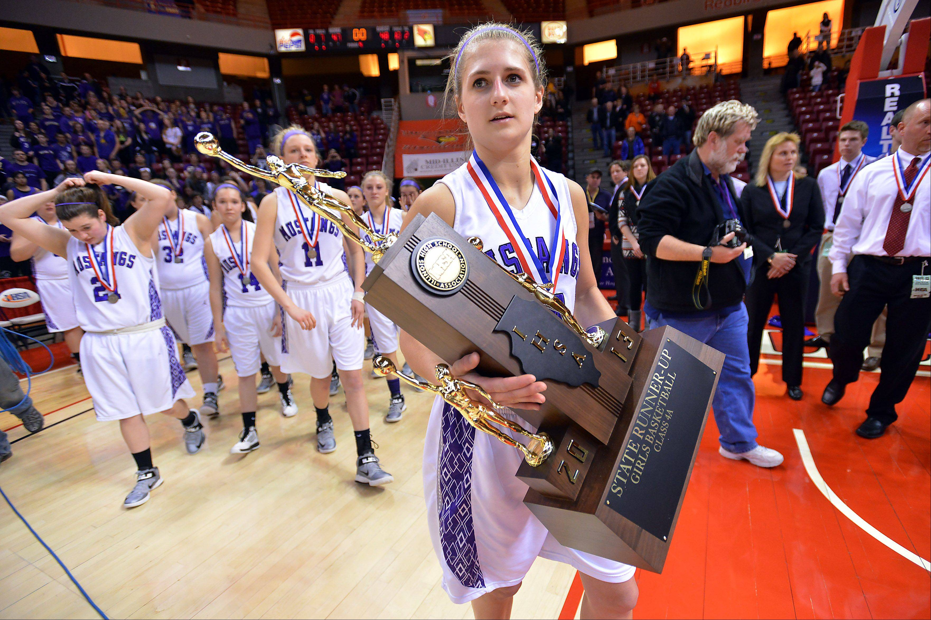 Rolling Meadows Alexis Glasgow carries the Class 4A runner-up trophy after Meadows got beat by buzzer beater shot by Marian in the final second in the Class 4A 2013 girls basketball championship game in Normal on Saturday.