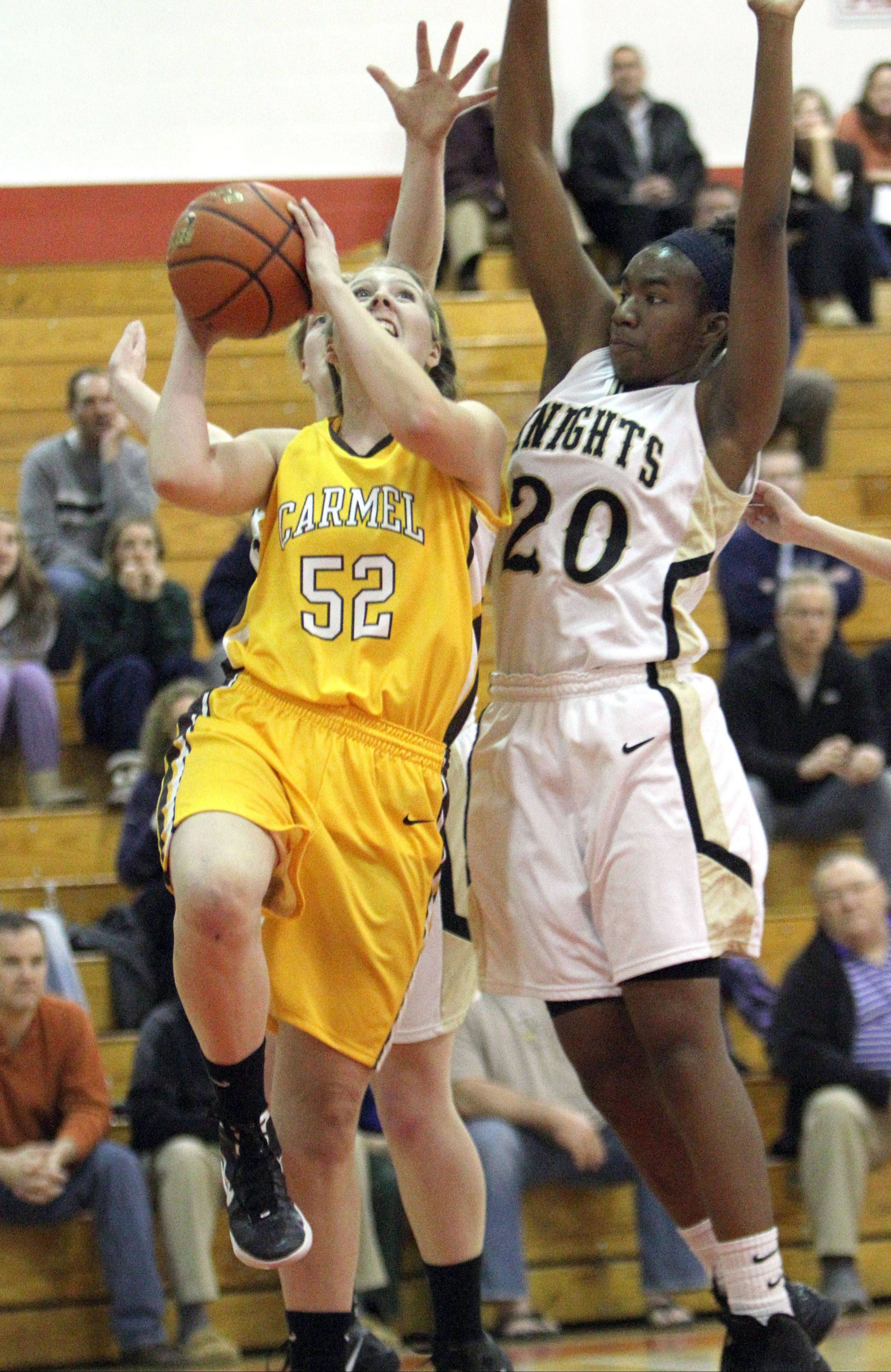Carmel's Kayla Quinn, left, drives on fellow All-Tall selection Brittney Thibeaux of Grayslake North during the Mundelein Turkey Tournament.