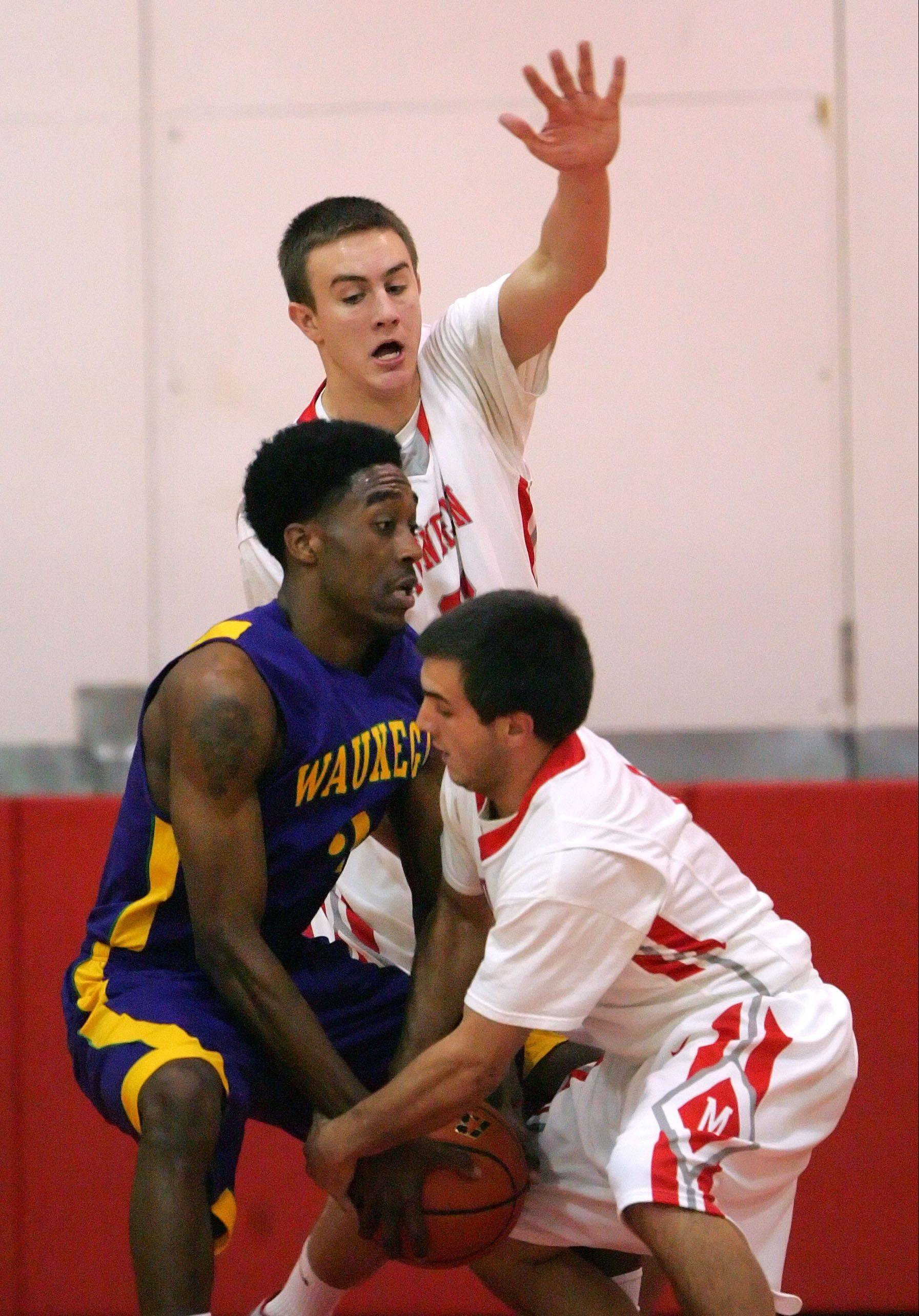 Mundelein's Sean O'Brien (All-Senior, All-Playmaker, All-Rebounding, All-Tall), back, and Thomas Gandolfi (All-Small) apply tough defense against Waukegan's Cornell Fort earlier this season.
