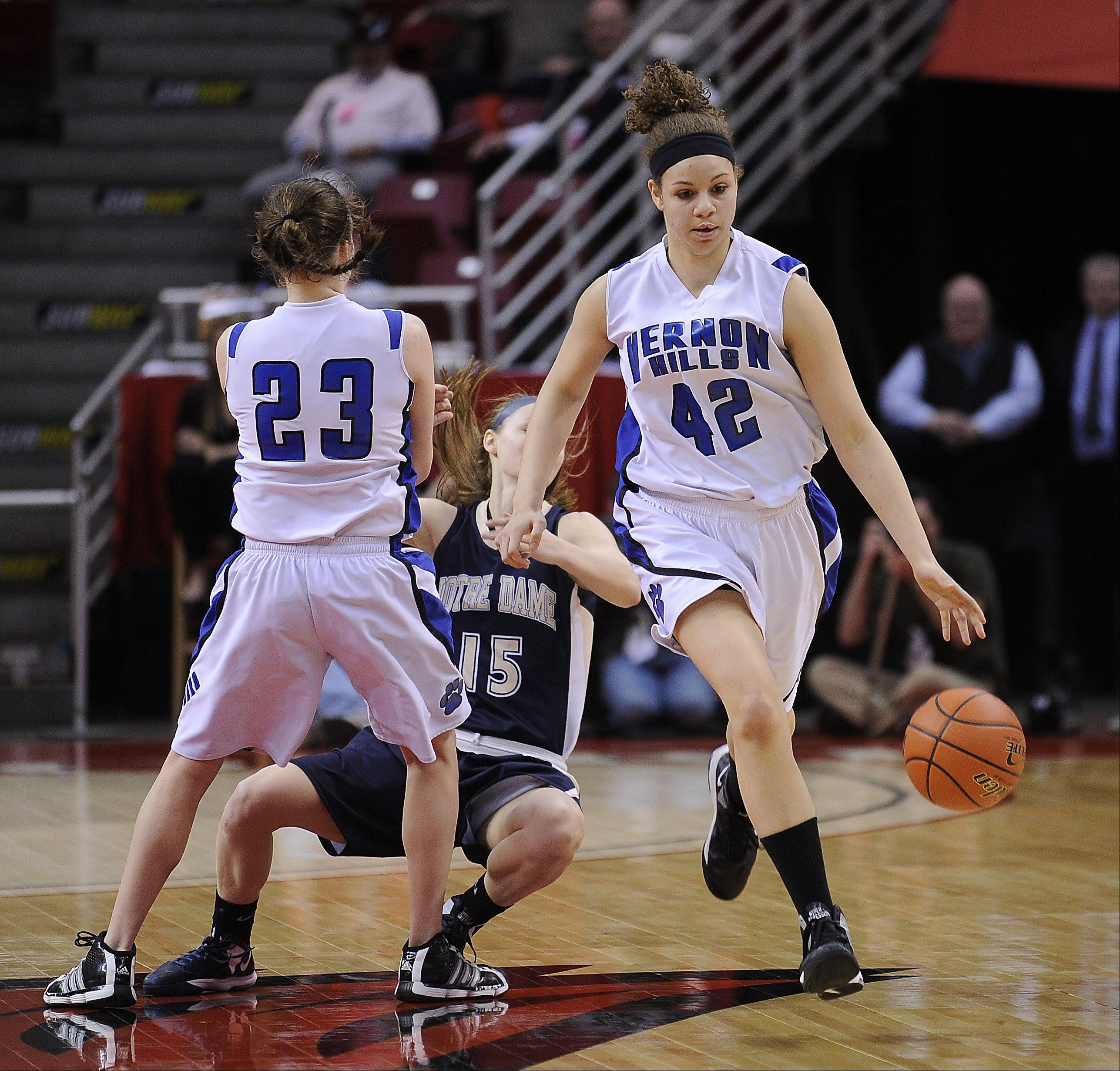 Vernon Hills Lauren Webb brings the ball down court as teammate Brie Bahlmann sets a block on Quincy Notre Dame Notre Dame's Kassidy Gengenbacher in the fourth quarter at the Class 3A state girls basketball championship in Normal on Saturday.