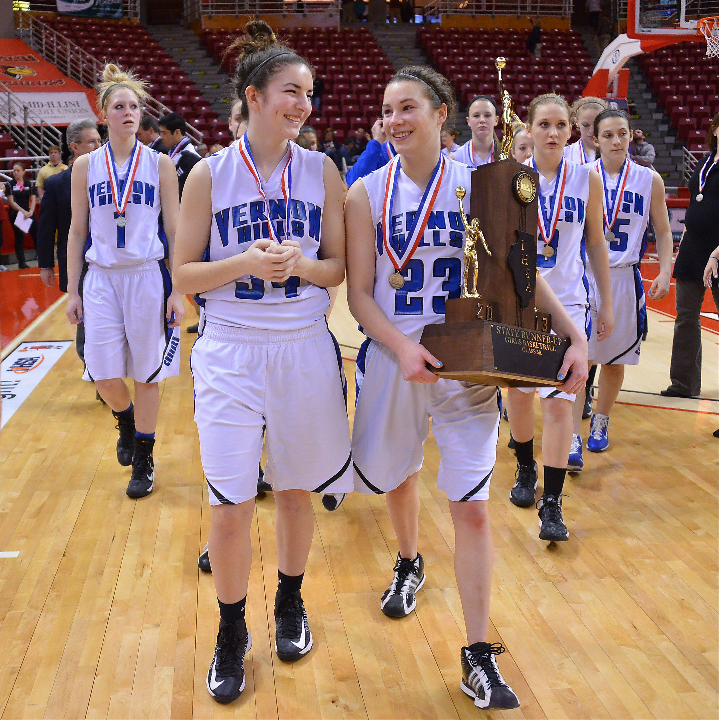 Vernon Hills Brie Bahlmann (right) and teammate Shannon Healey are all smiles as they walk with the trophy off the floor winning second place in the Class 3A state girls basketball championship game in Normal on Saturday.