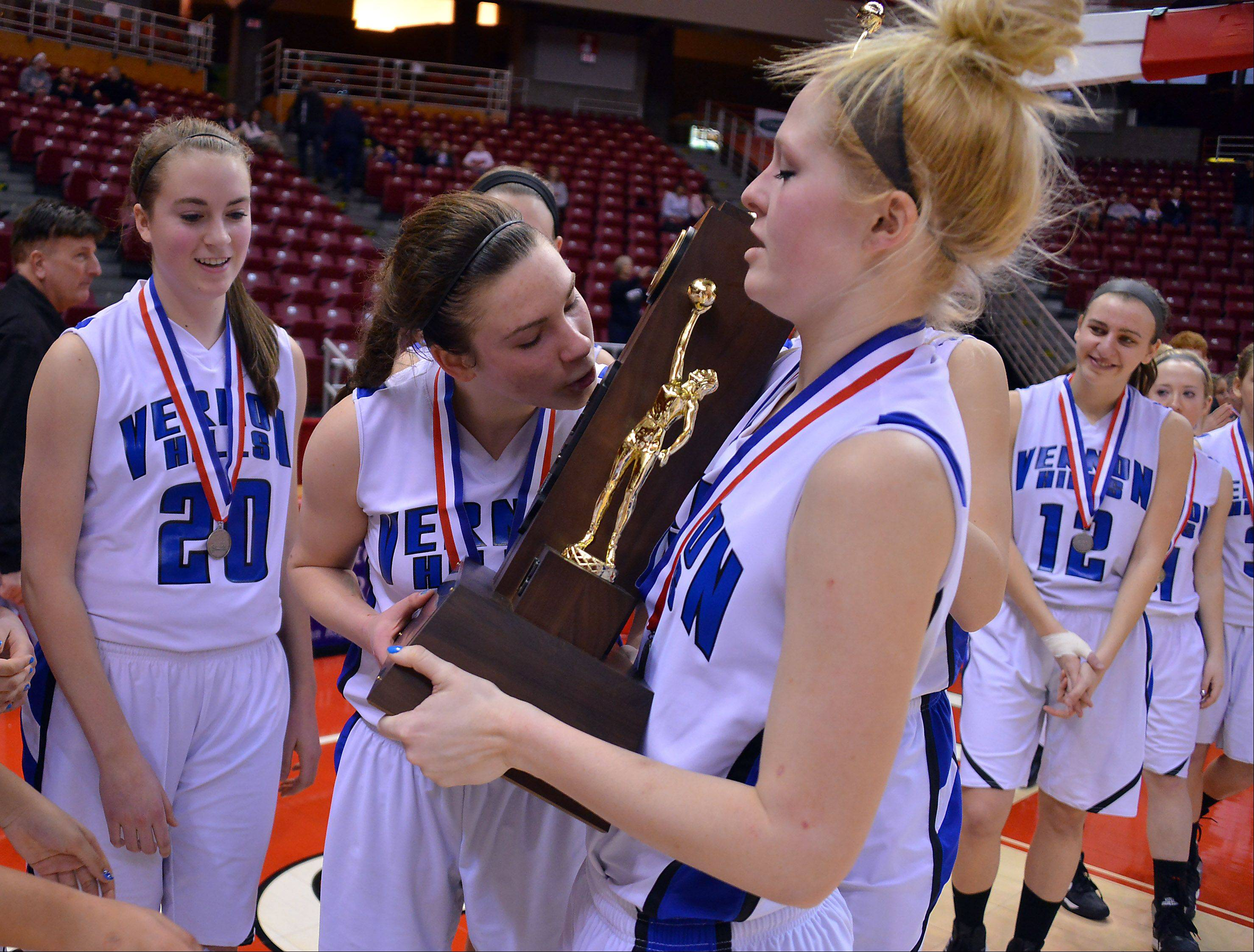 Vernon Hills' Brie Bahlmann kisses the second place trophy as teammate Sydney Smith holds it after they lost to Quincy Notre Dame in the Class 3A state girls basketball championship game in Normal on Saturday.