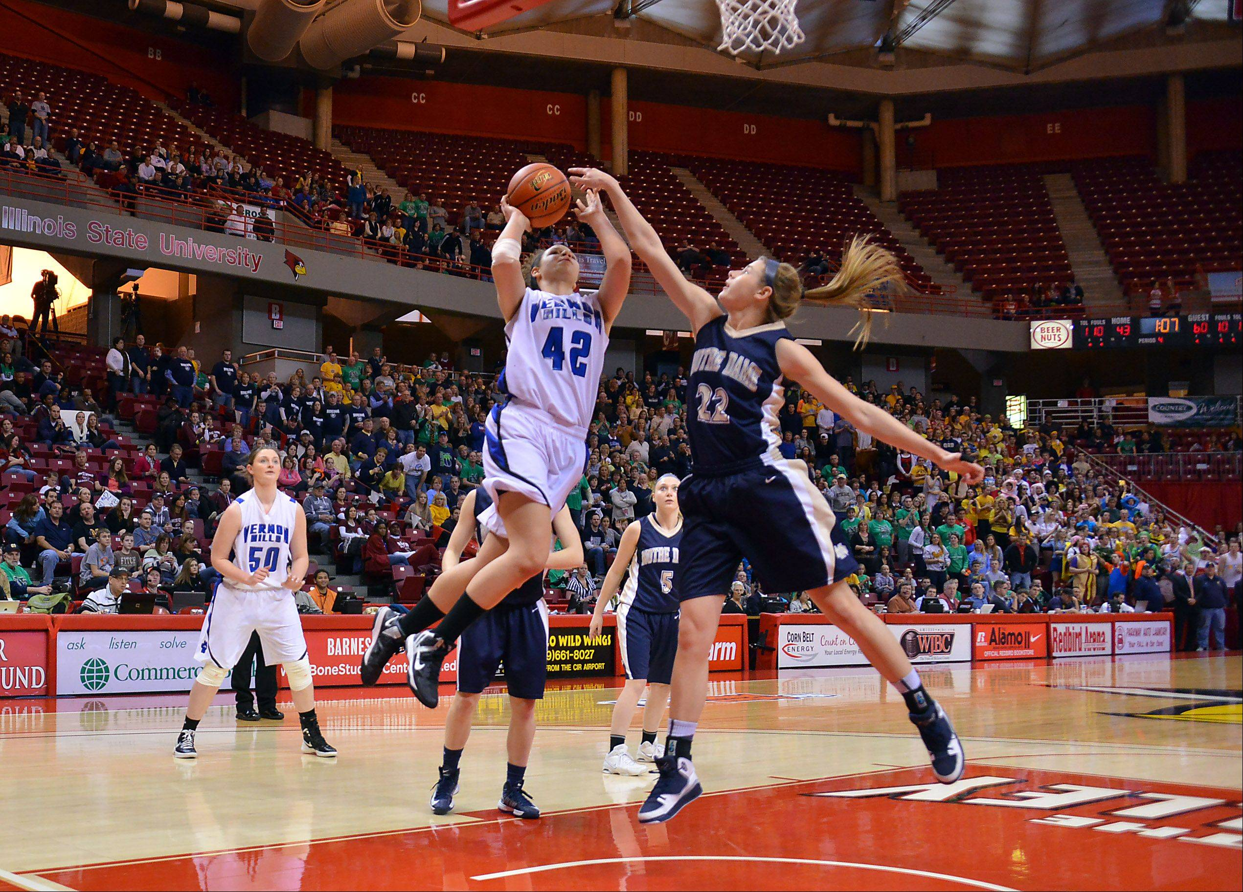 Vernon Hills Lauren Webb battles Quincy Notre Dame's Jordan Frericks under the basket late in the fourth quarter at the Class 3A state girls basketball championship in Normal on Saturday.