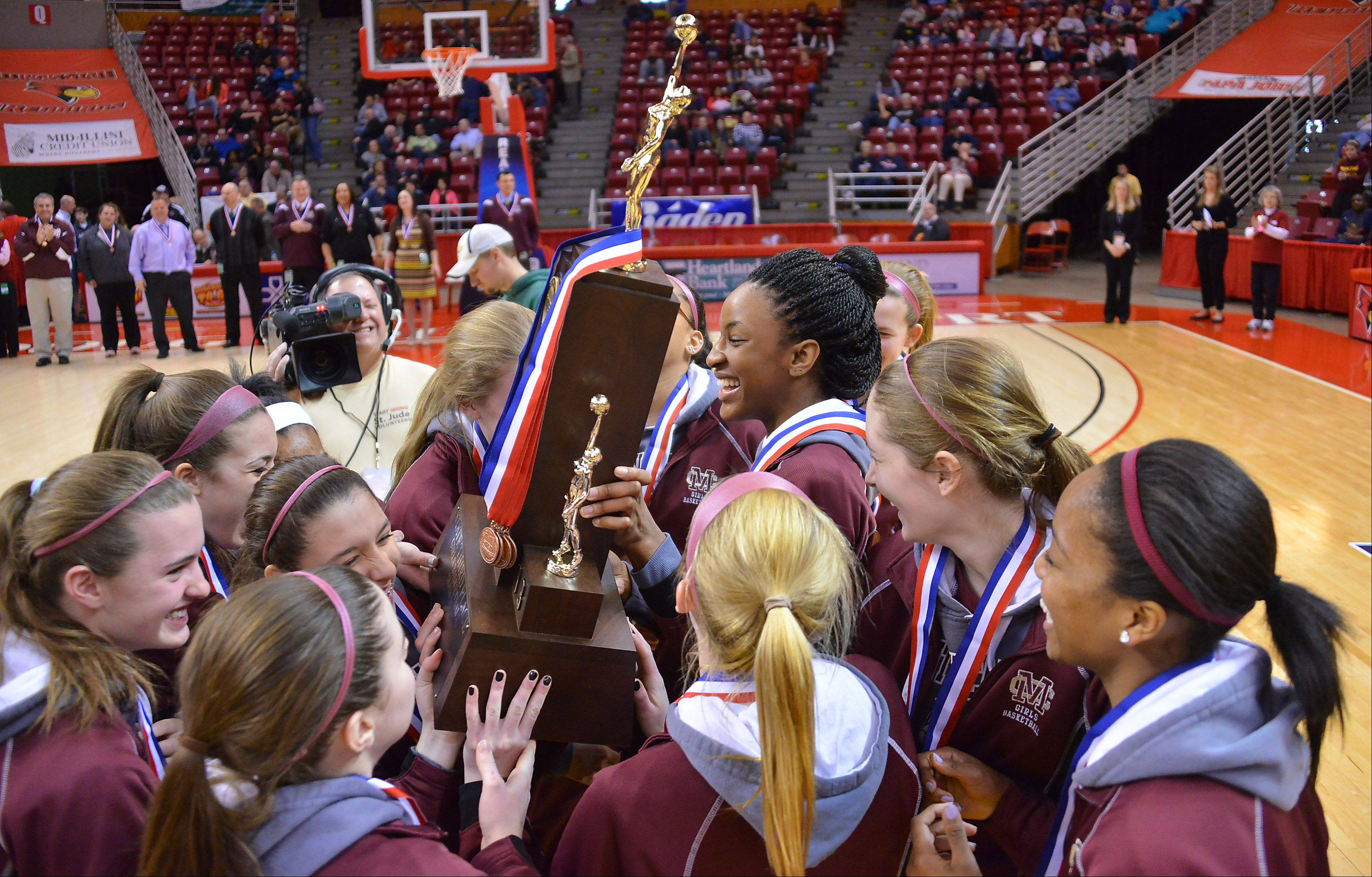 Montini carries off the third place trophy in the Class 3A girls state basketball third place game in Normal on Saturday.