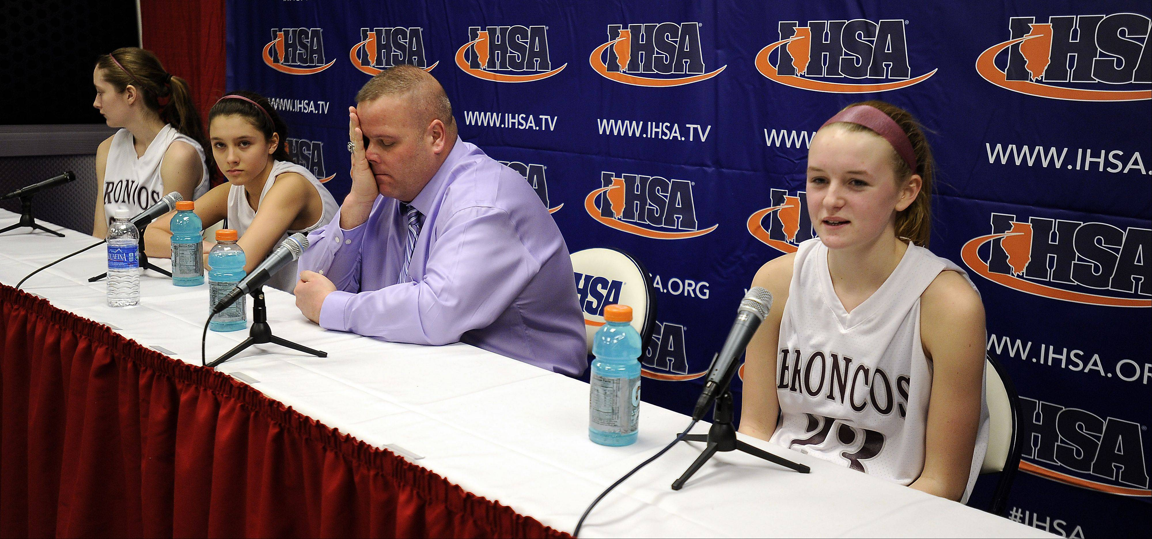 Montini's Lea Kerstein talks to the media after winning the third place game against Morton while coach Jason Nichols feels the sting of not winning like in past years in the Class 3A girls state basketball third place game in Normal on Saturday.