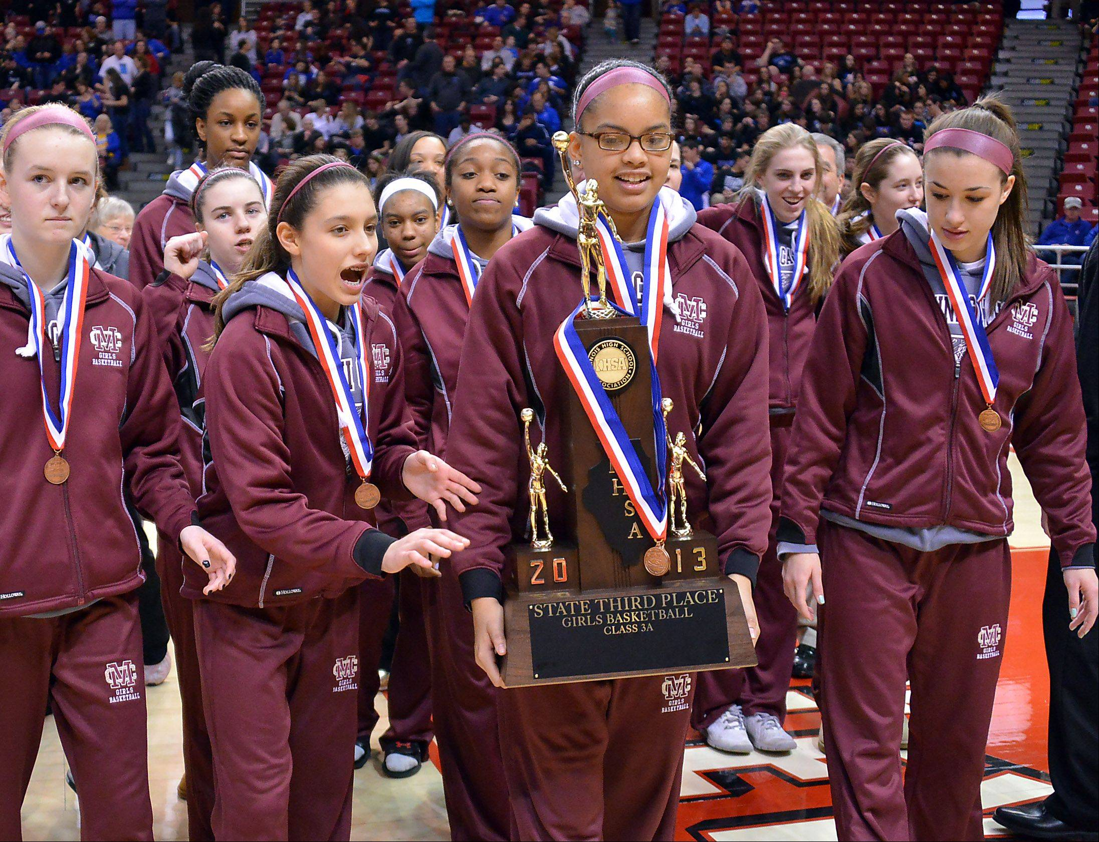 Montini's Rainey Kuykendall and the rest of her teammates carry off the third place trophy in the Class 3A girls state basketball third place game in Normal on Saturday.