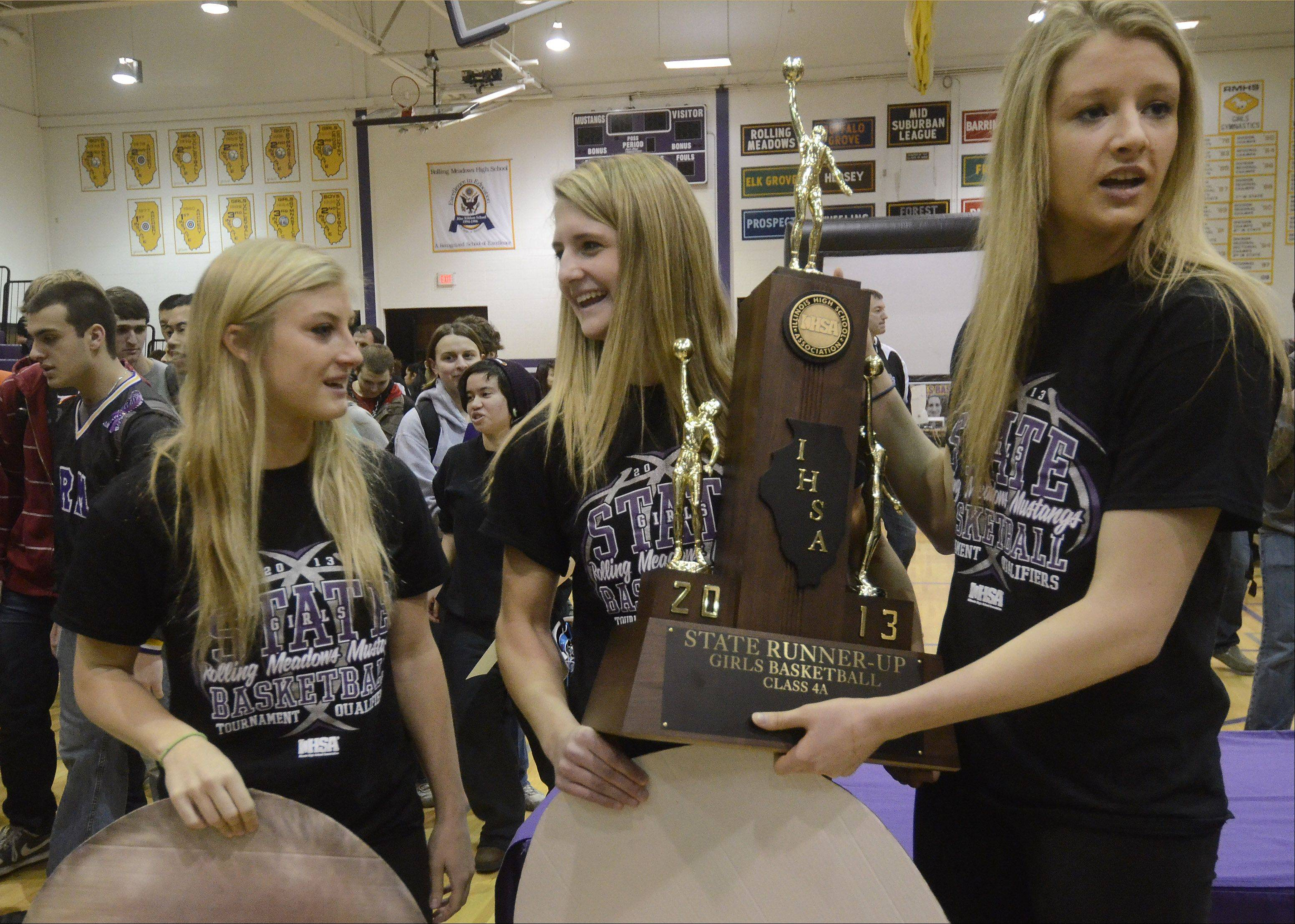Rolling Meadows High School girls basketball captains Jackie Kemph, Alexis Glasgow and Jenny Vliet hold the Class 4A runner up trophy during a school celebration for the team Monday morning. The team is returning nearly all of its players next year, giving hope for another run for the state title.
