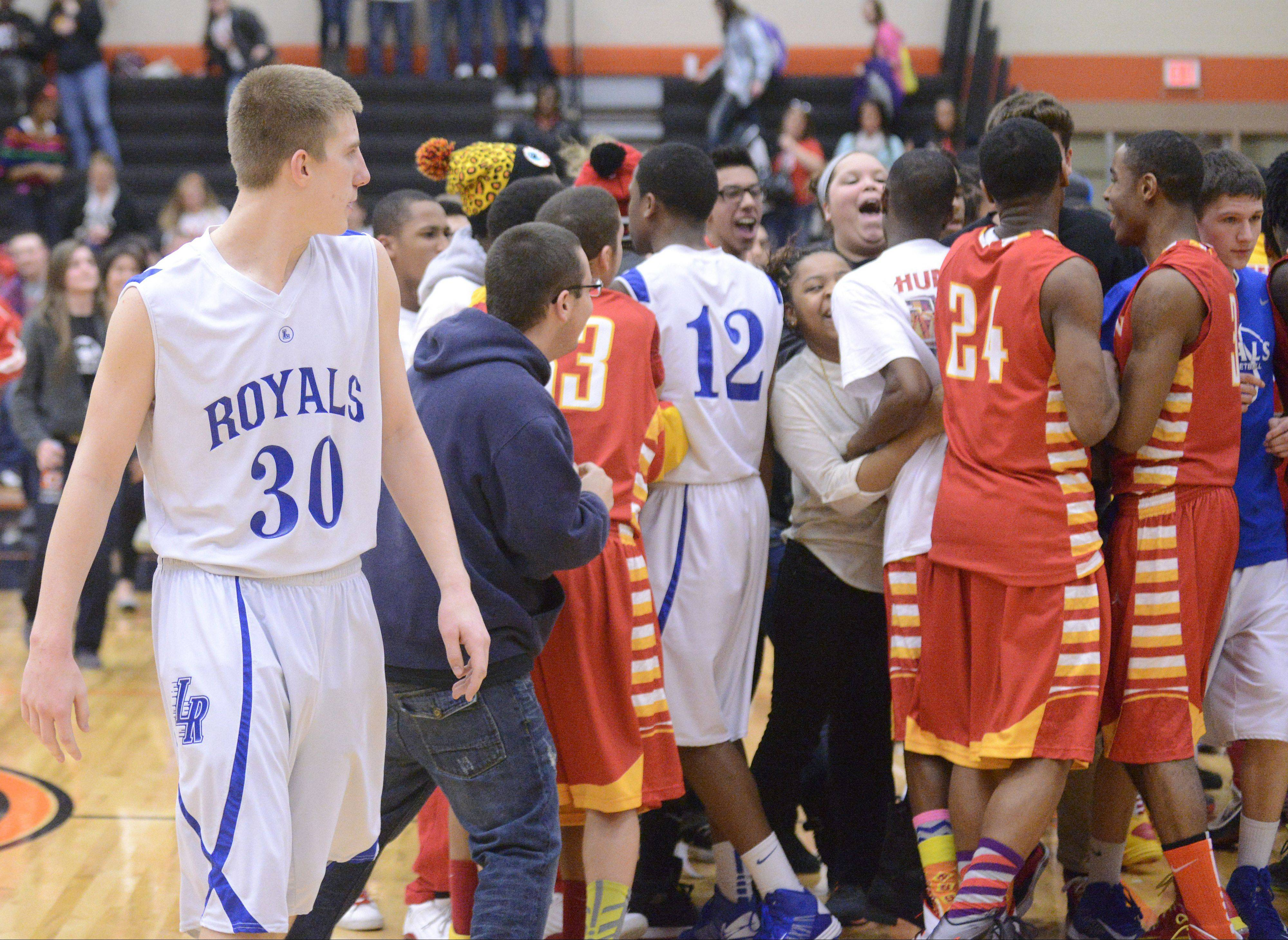 Larkin's Brayden Royse (30) walks among celebrating teammates and fans from Rockford Jefferson, as his own teammate, Hannibal Marshall, 12, gets caught up in the crowd, after the Royals' loss to the J-Hawks in the Class 4A DeKalb sectional semifinals on Wednesday.