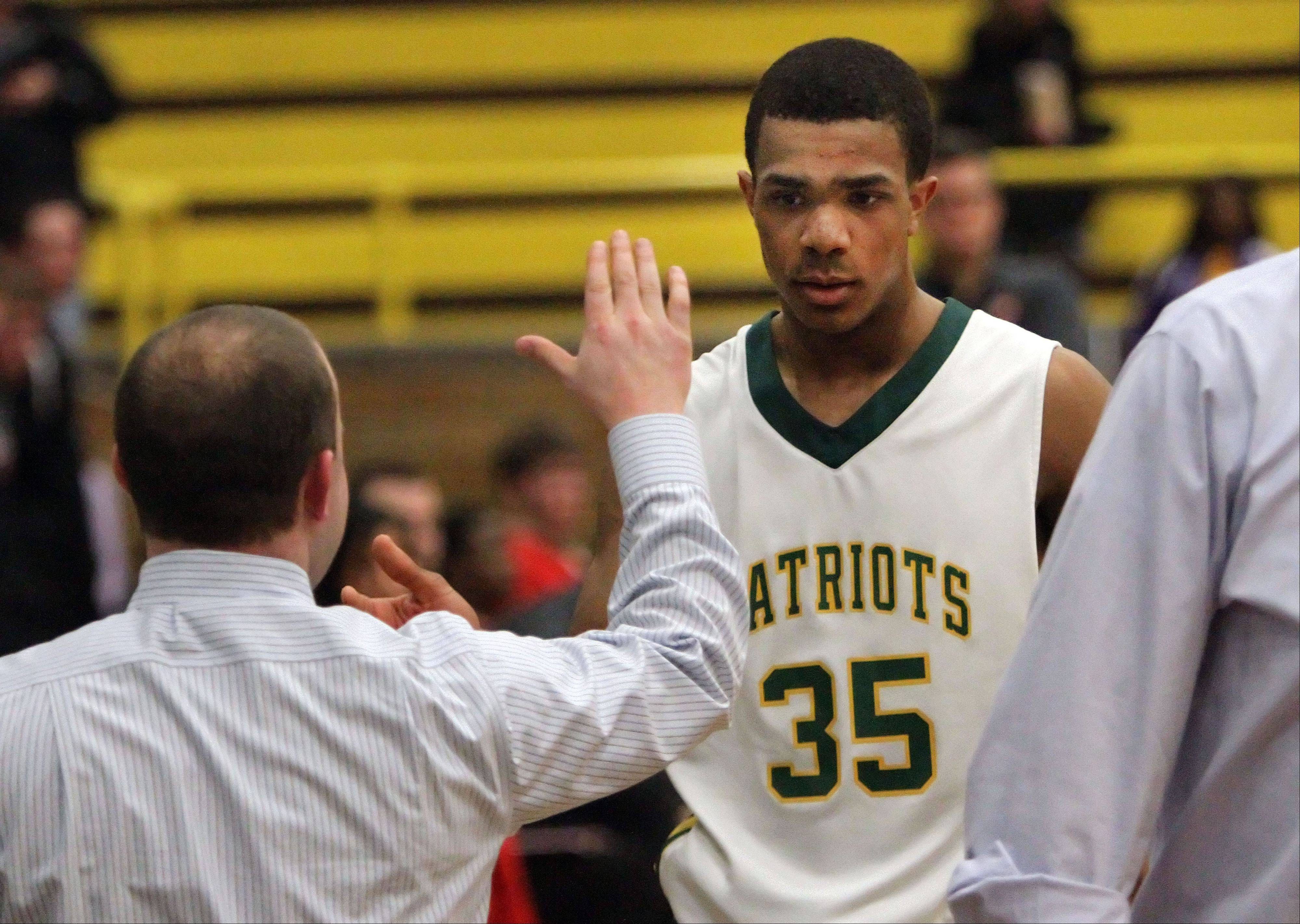 Stevenson's Connor Cashaw gets high fives from the bench during the Patriots' win over Mundelein in the Class 4A Waukegan sectional semifinals Wednesday night.