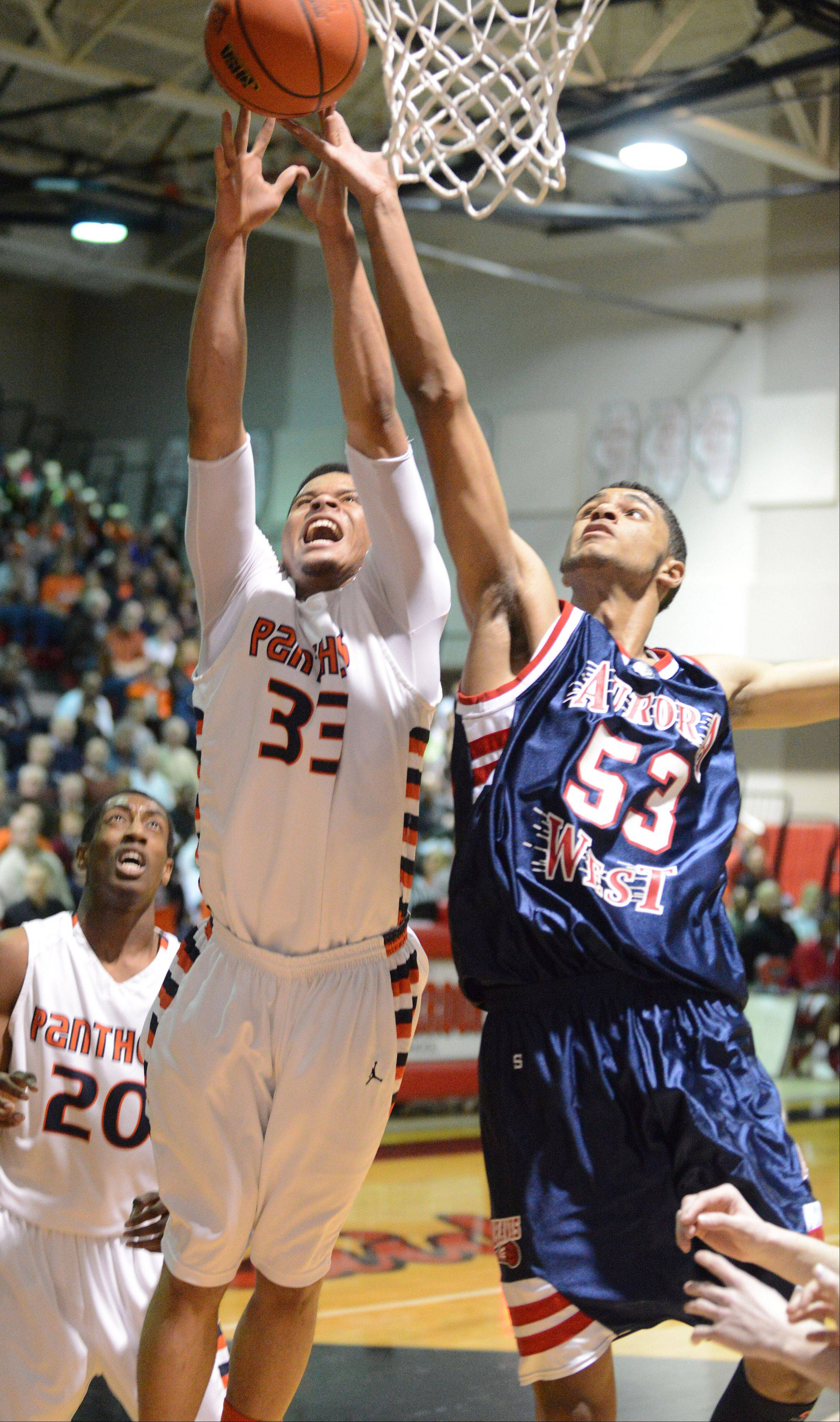 Darion Reddick of Oswego,left, and Joshua Mcauley of West Aurora go for a rebound during the West Aurora vs. Oswego game at the Bolingbrook sectional semifinals Wednesday.