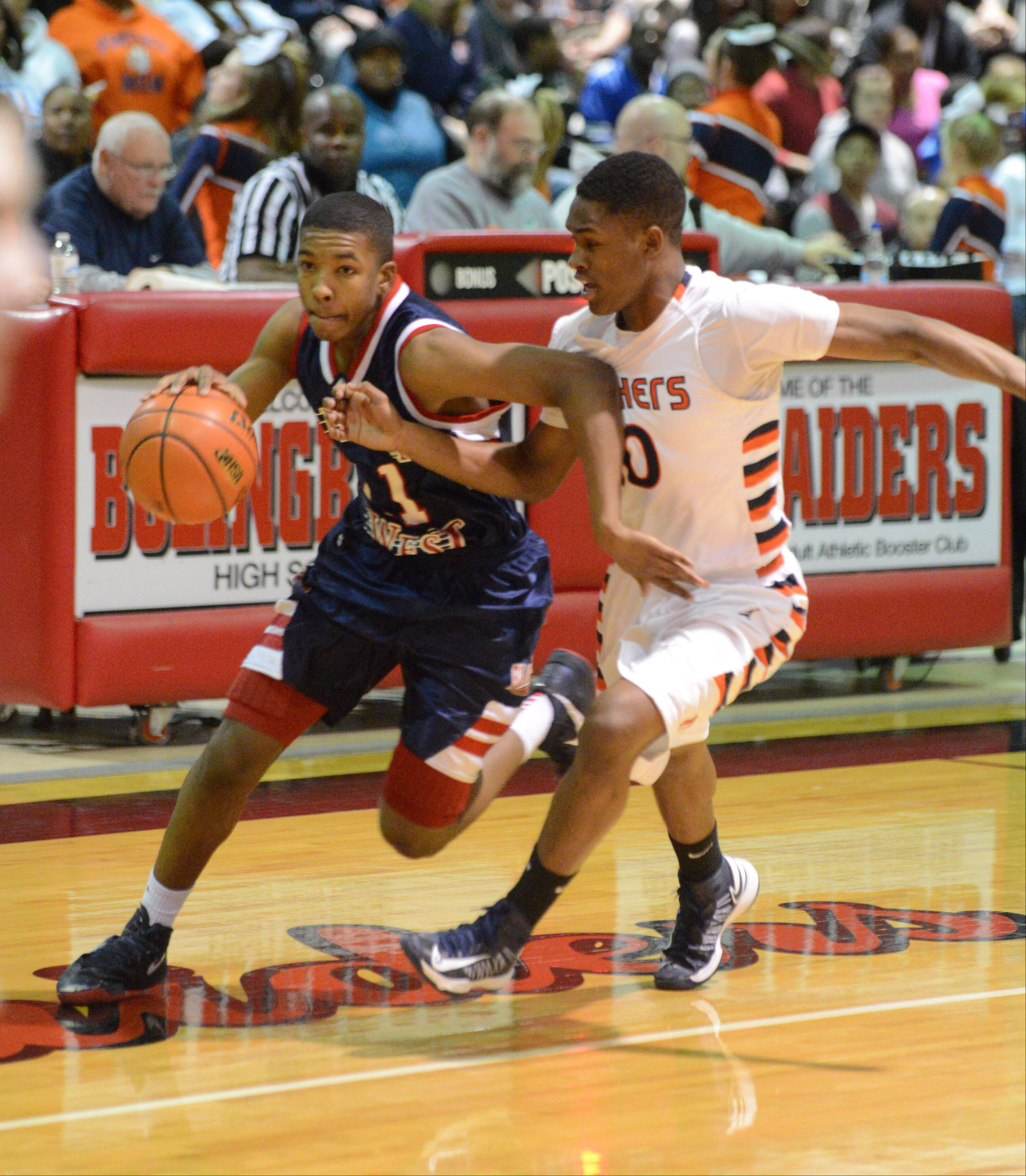Jontrel Walker of West Aurora moves the ball while Jamaal Richardson of Oswego moves alongside him. This took place during the West Aurora vs. Oswego game at the Bolingbrook sectional semifinals.