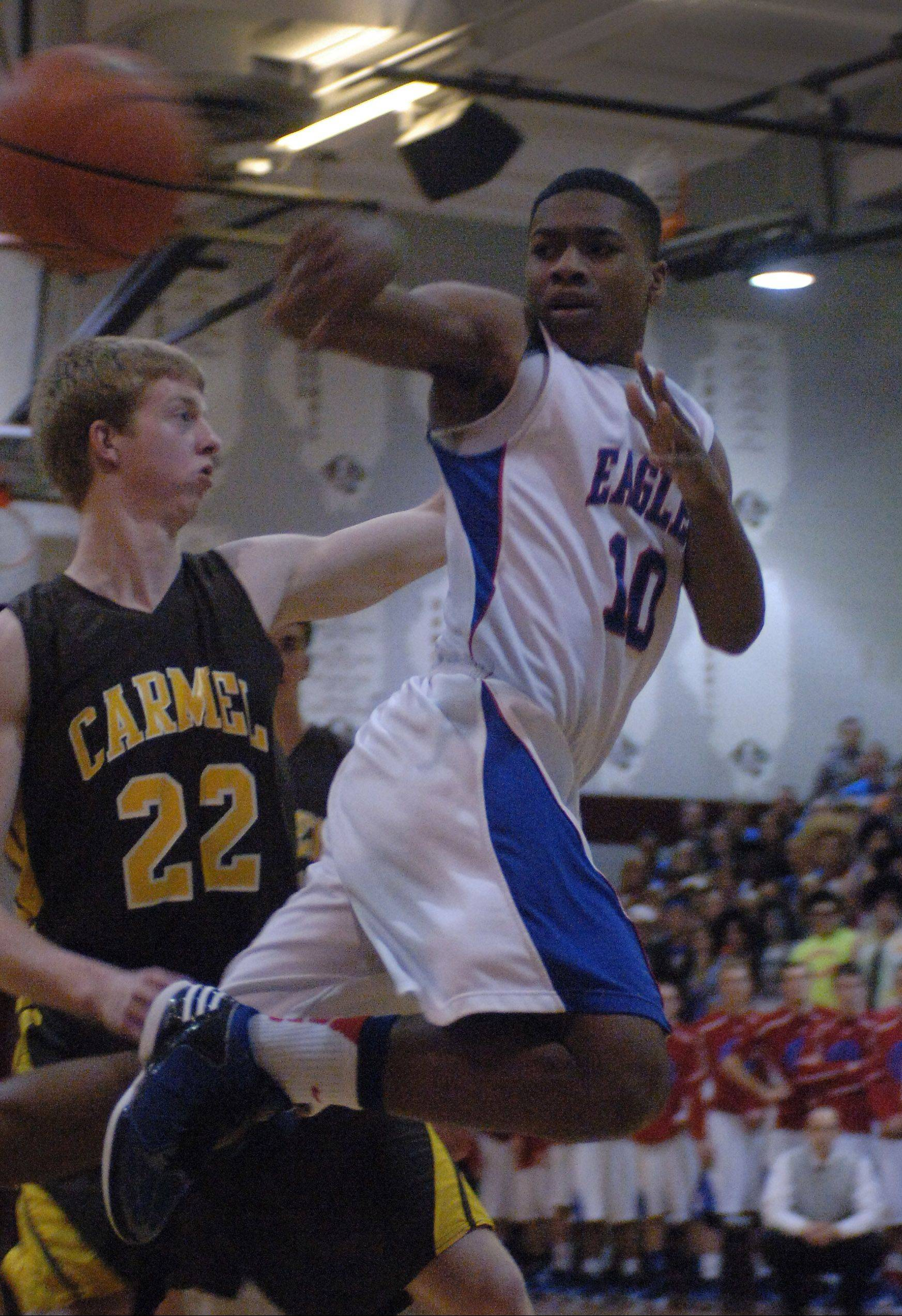 Lakes' Andrew Spencer passes around Carmel's Michael Barr during Thursday's Class 3A sectional semifinal game in Antioch.