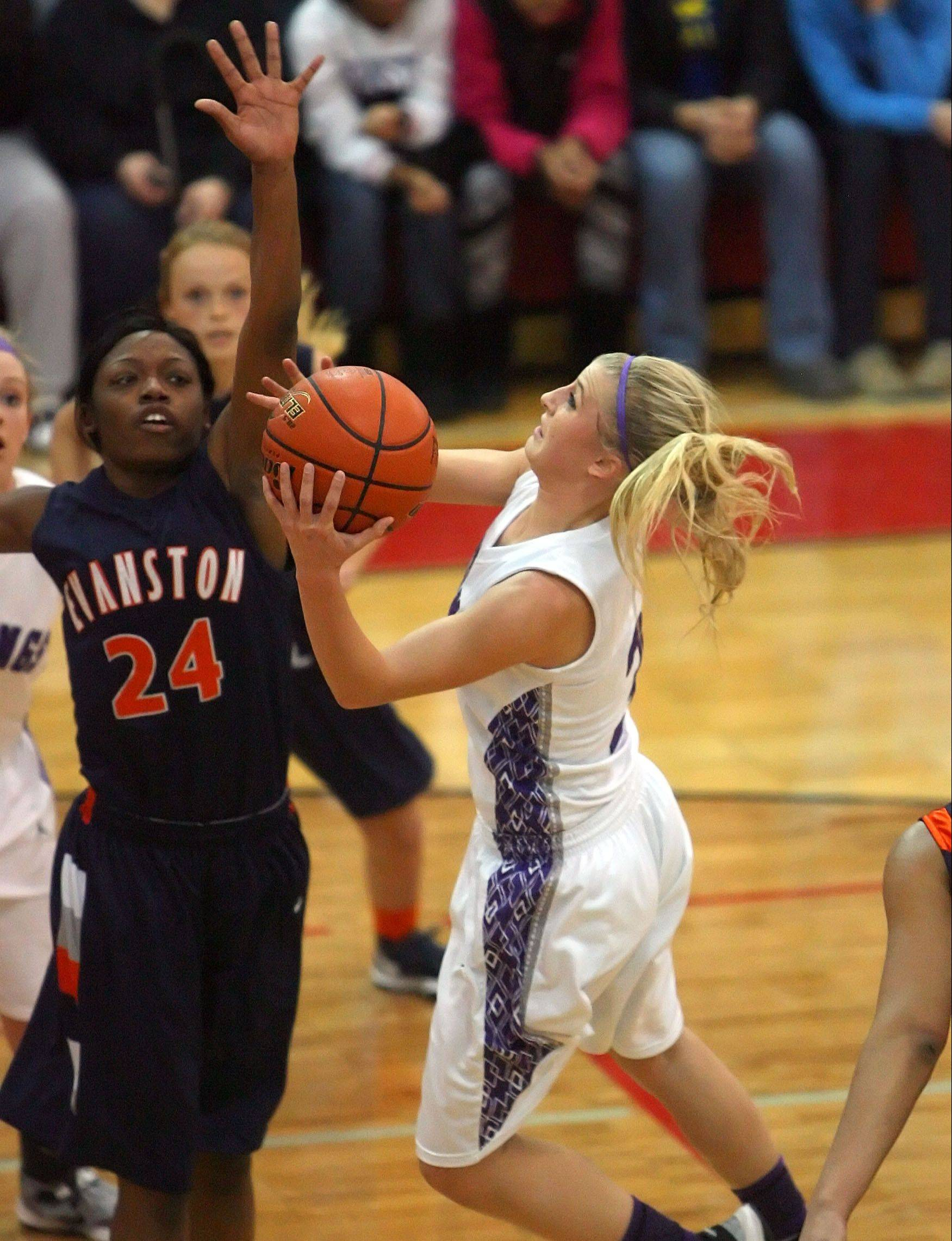 Rolling Meadows junior Jackie Kemph, right, glides to the basket with Evanston's Sierra Clayborn defending in Class 4A Niles West supersectional action. Kemph captains the Daily Herald's girls basketball all-area team for the Northwest suburbs.