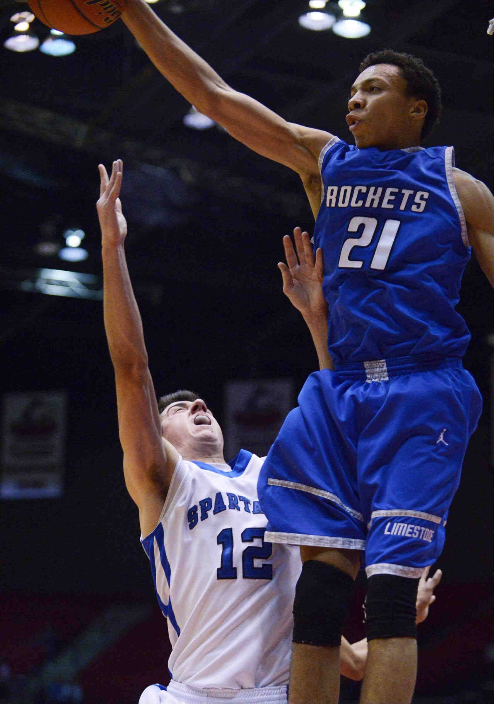 St. Francis' Tim Zettinger has a desperation shot blocked by Bartonville Limestone's David Anderson Tuesday in the 3A Dekalb supersectional game at the Northern Illinois Convocation Center.