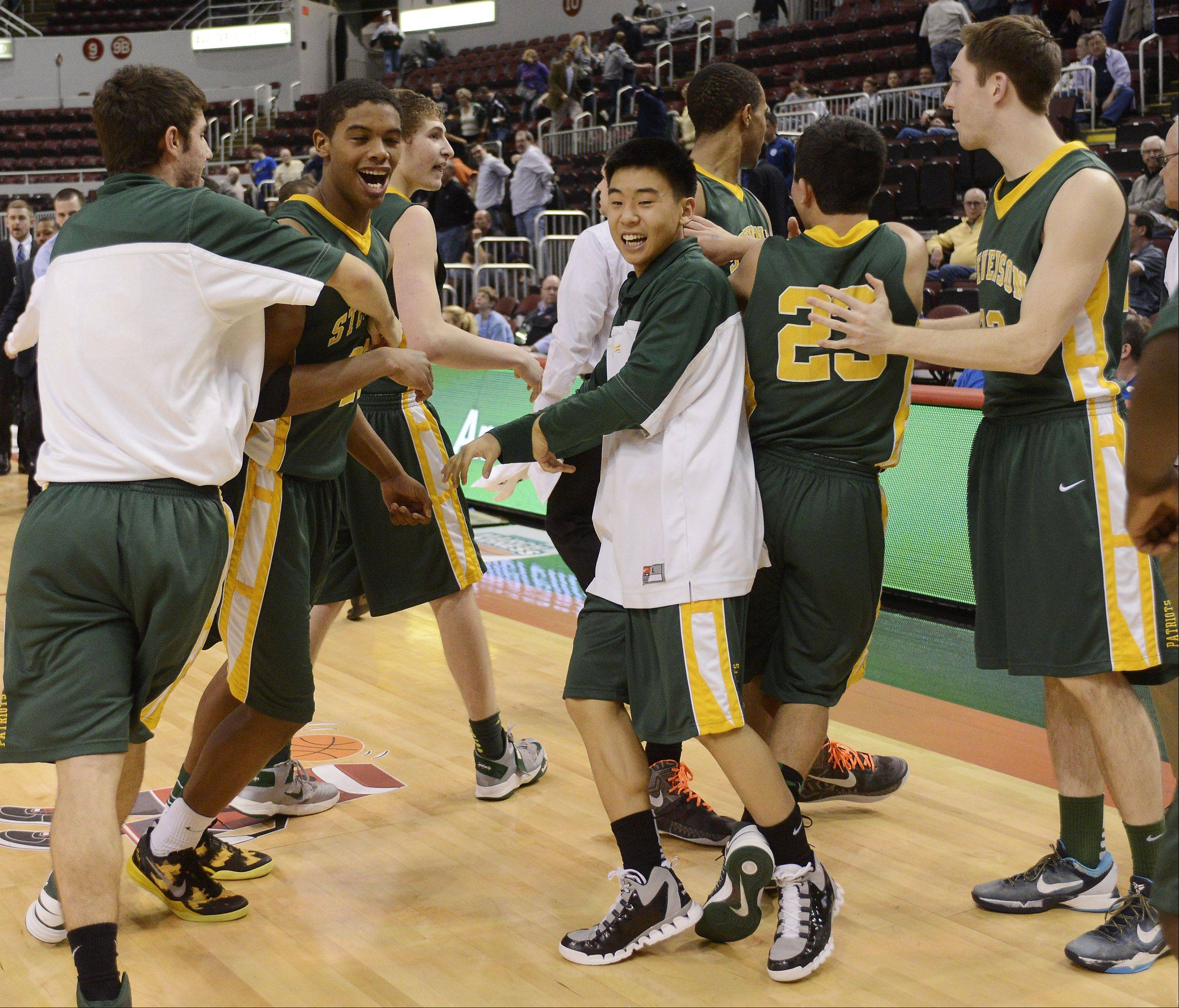 Stevenson celebrates its 60-49 victory over Edwardsville during the Class 4A boys basketball semifinals at Carver Arena in Peoria on Friday.