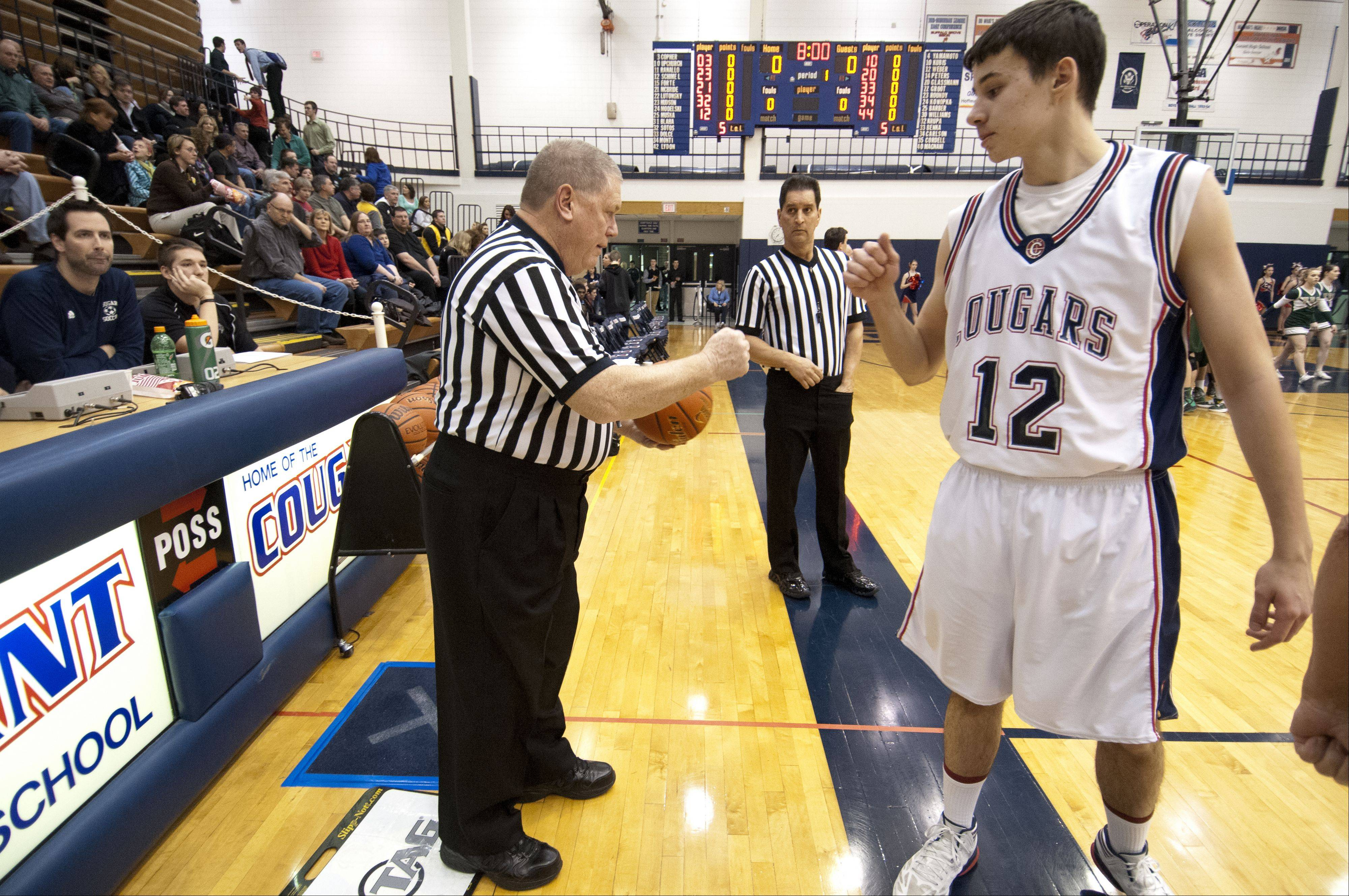 IHSA referee Rick Bieterman greets players with a fist bump before the start of a game between Fremd and Conant.