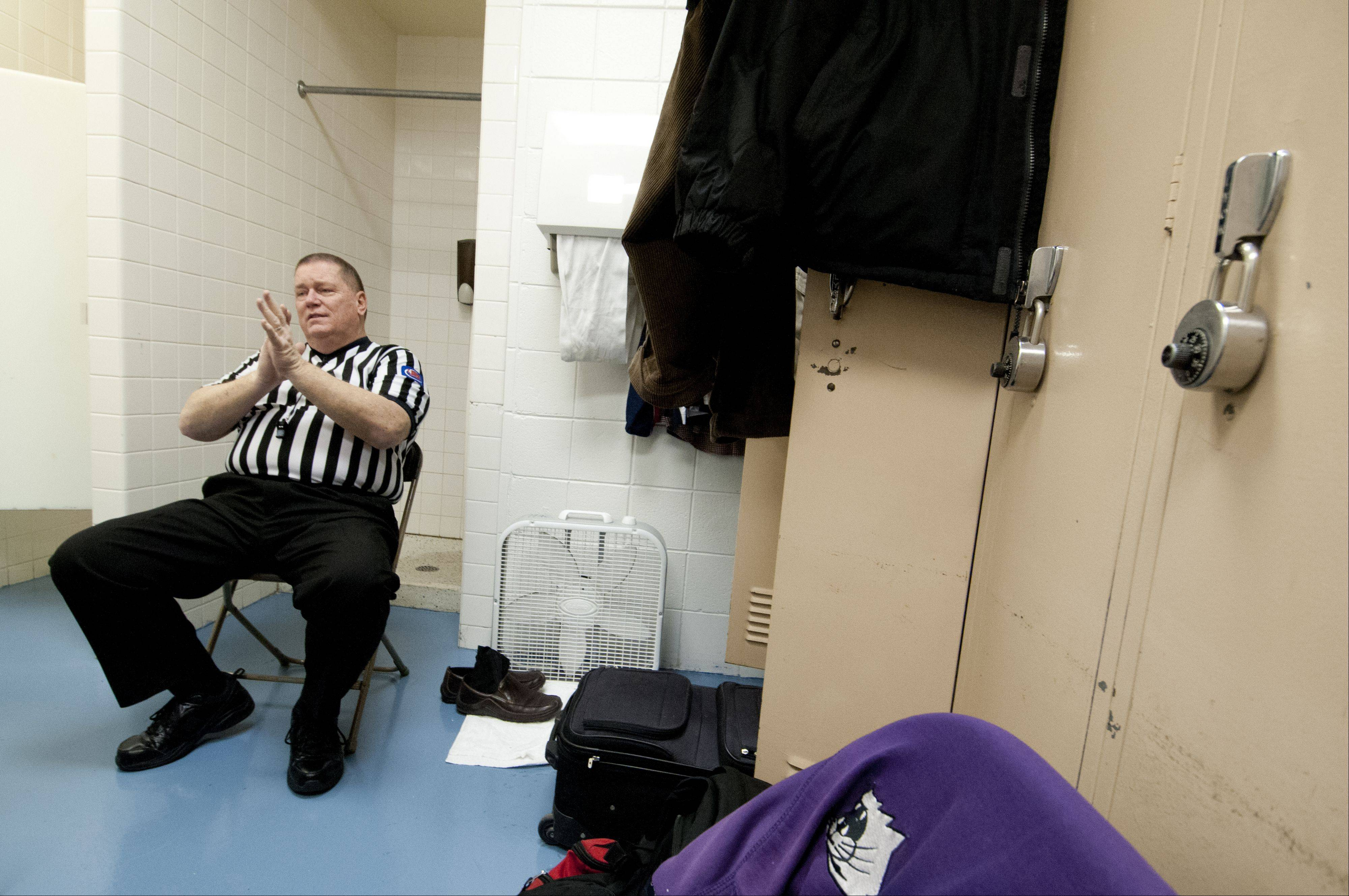 Longtime IHSA referee Rick Bieterman talks with his fellow referees during halftime in the referee locker room at Conant High School.