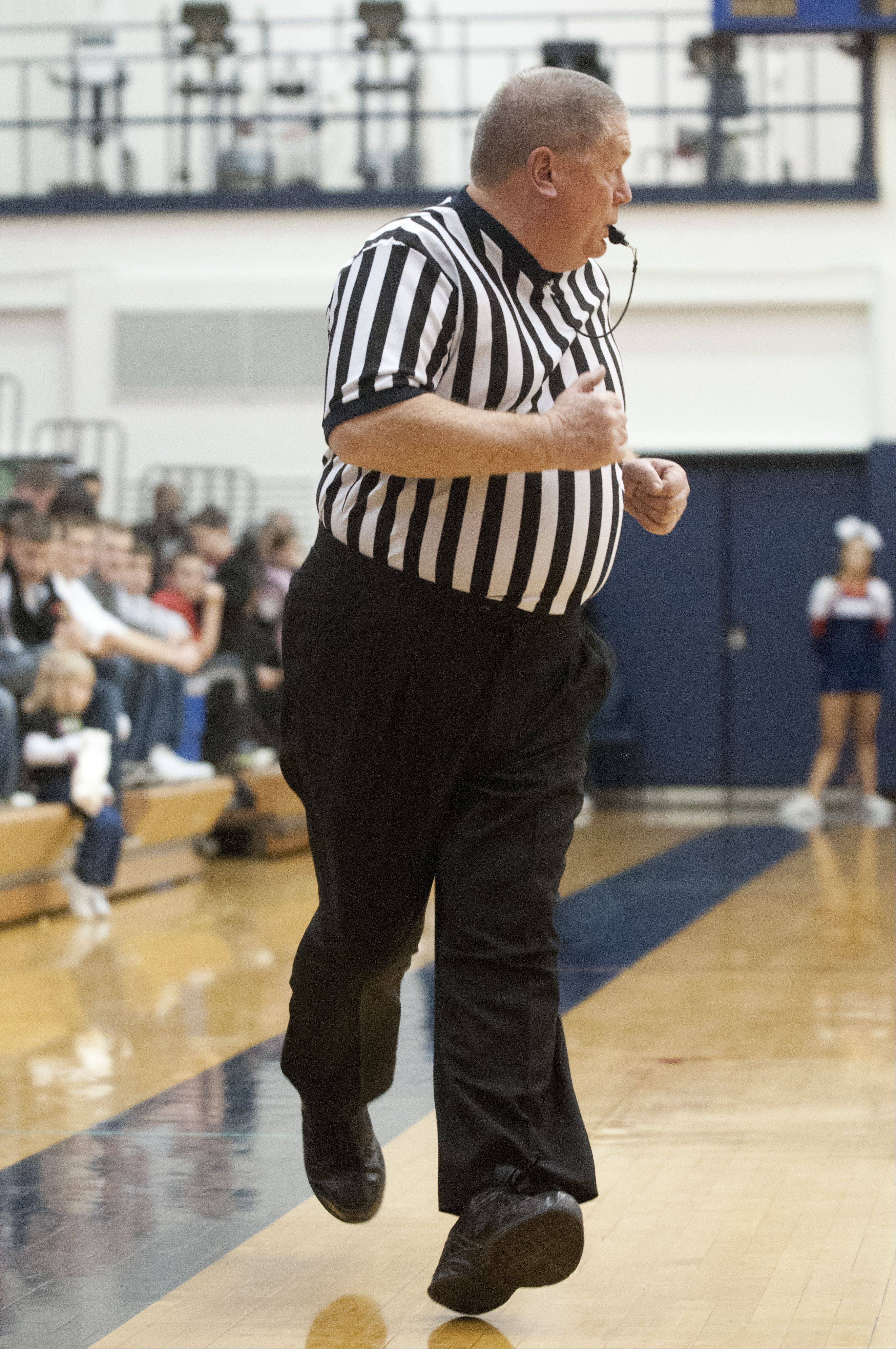 Rick Bieterman jogs up the court as he referees a game between Fremd and Conant high schools.