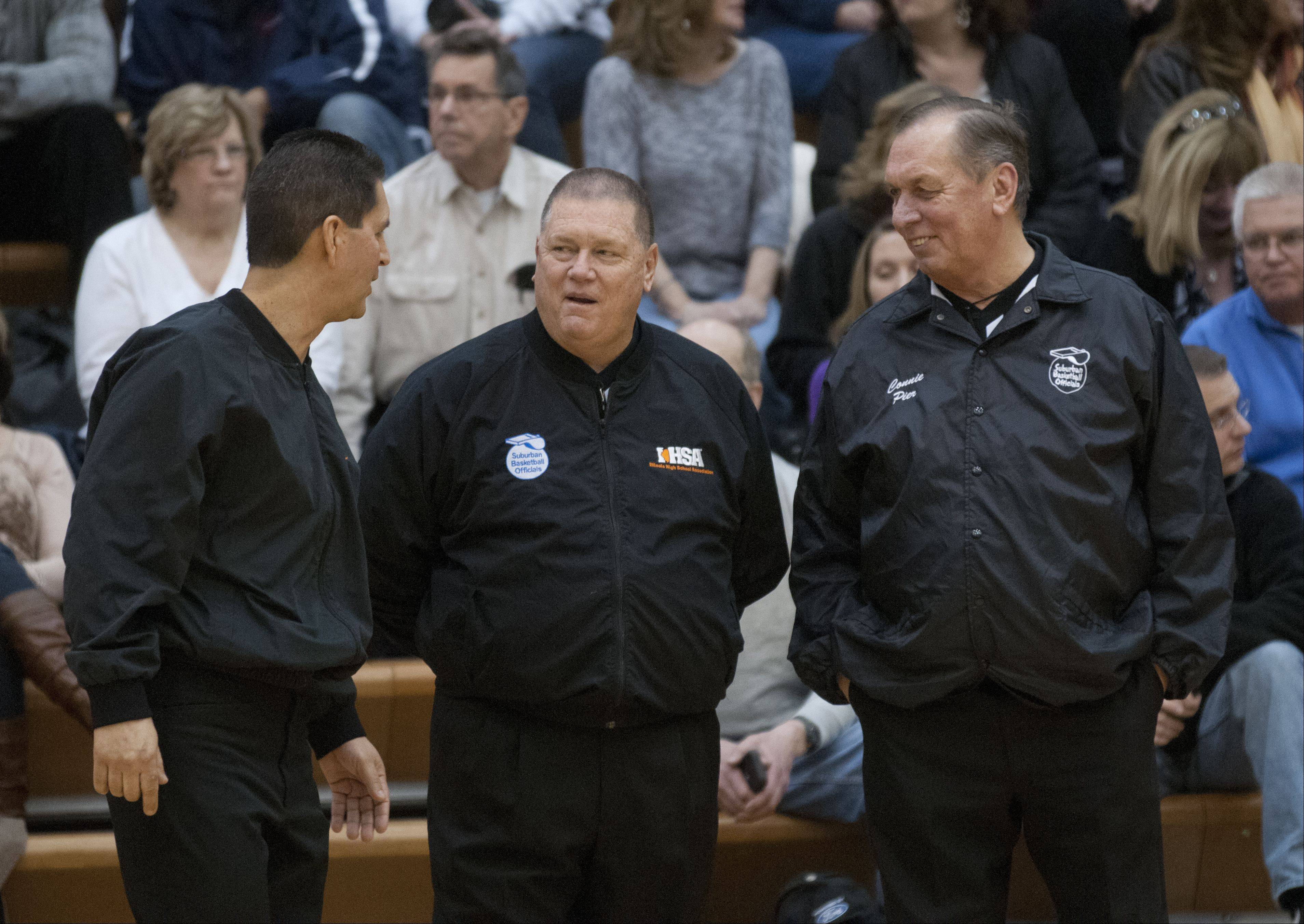 Rick Bieterman, center, talks with fellow referees Ernie Flores and Connie Pier before the start of the game between Fremd and Conant high schools. Bieterman has worked with these two refs for years and views them as his teammates.