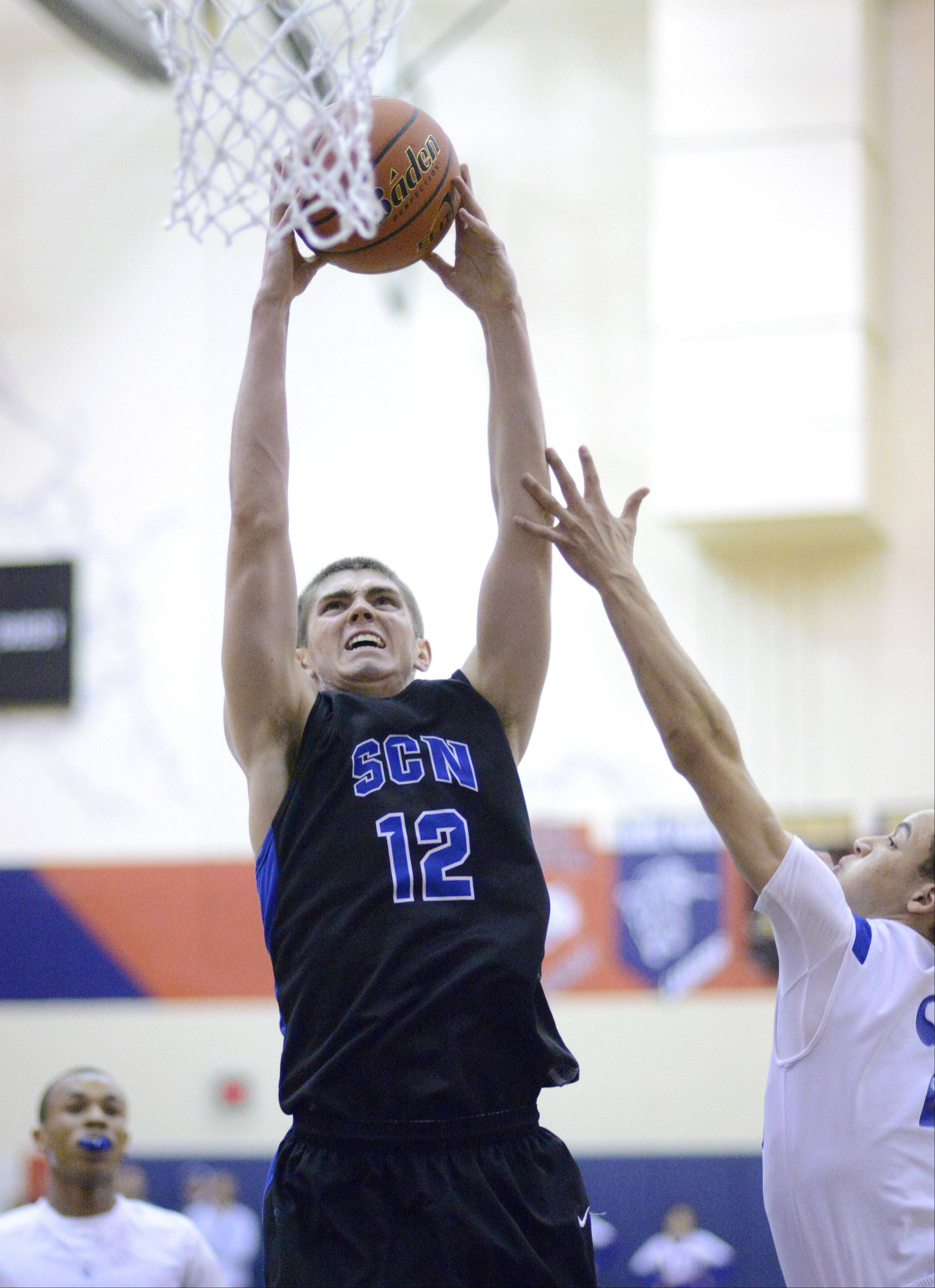 St. Charles North's Quinten Payne dunks a shot over Larkin's Derrick Streety this past season. Payne announced Tuesday he will attend Ball State to play his college basketball.