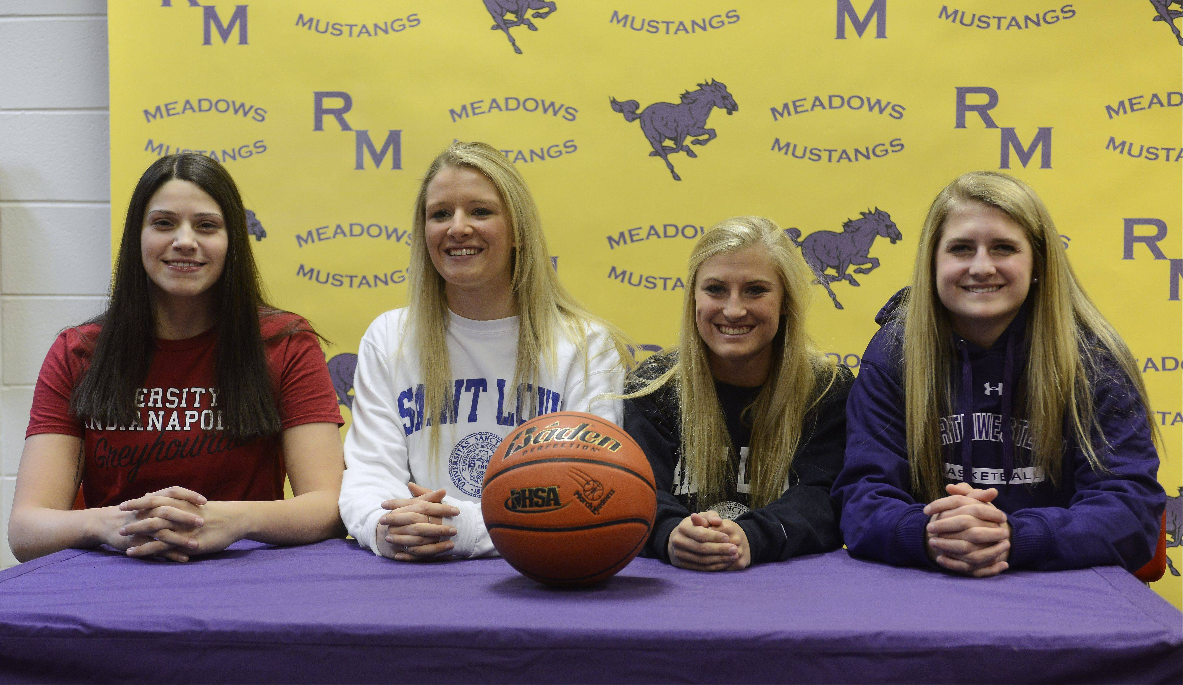 Left to right, Ashley Montanez (University of Indianapolis), Jenny Vliet and Jackie Kemph (St. Louis) and Alexis Glasgow (Northwestern) are seated together during a college letter of intent signing ceremony at Rolling Meadows High School on Wednesday.